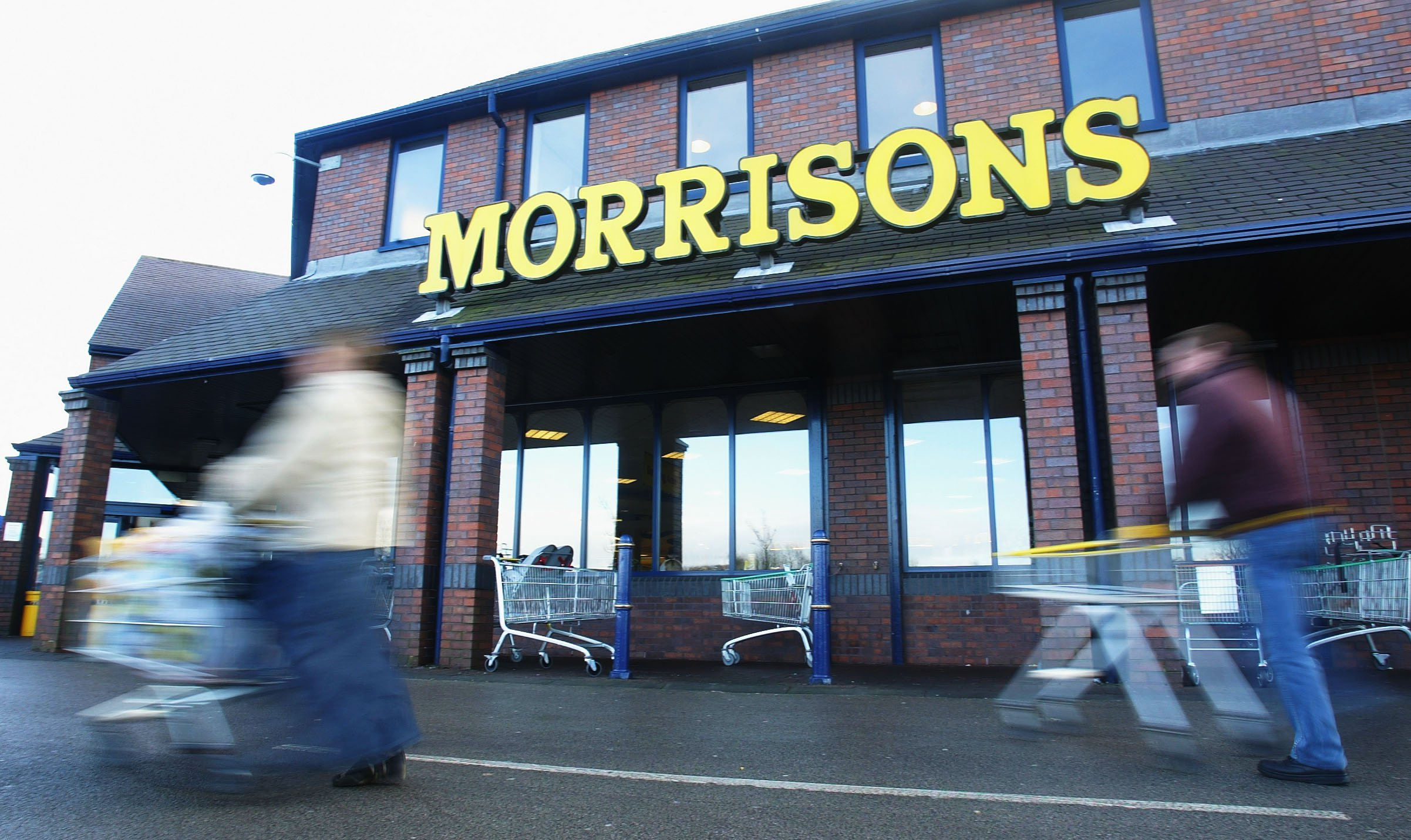 ROCHDALE - JANUARY 9: A shopper pushes her cart outside a Morrisons supermarket January 9, 2003 in Rochdale, Lancashire. The mid-size British supermarket chain, Morrisons, announced its bid to overtake rival Safeway in a 2.9 billion pound deal that would combine the firm with 589 stores and a 16 percent market share. (Photo by Laurence Griffiths/Getty Images)