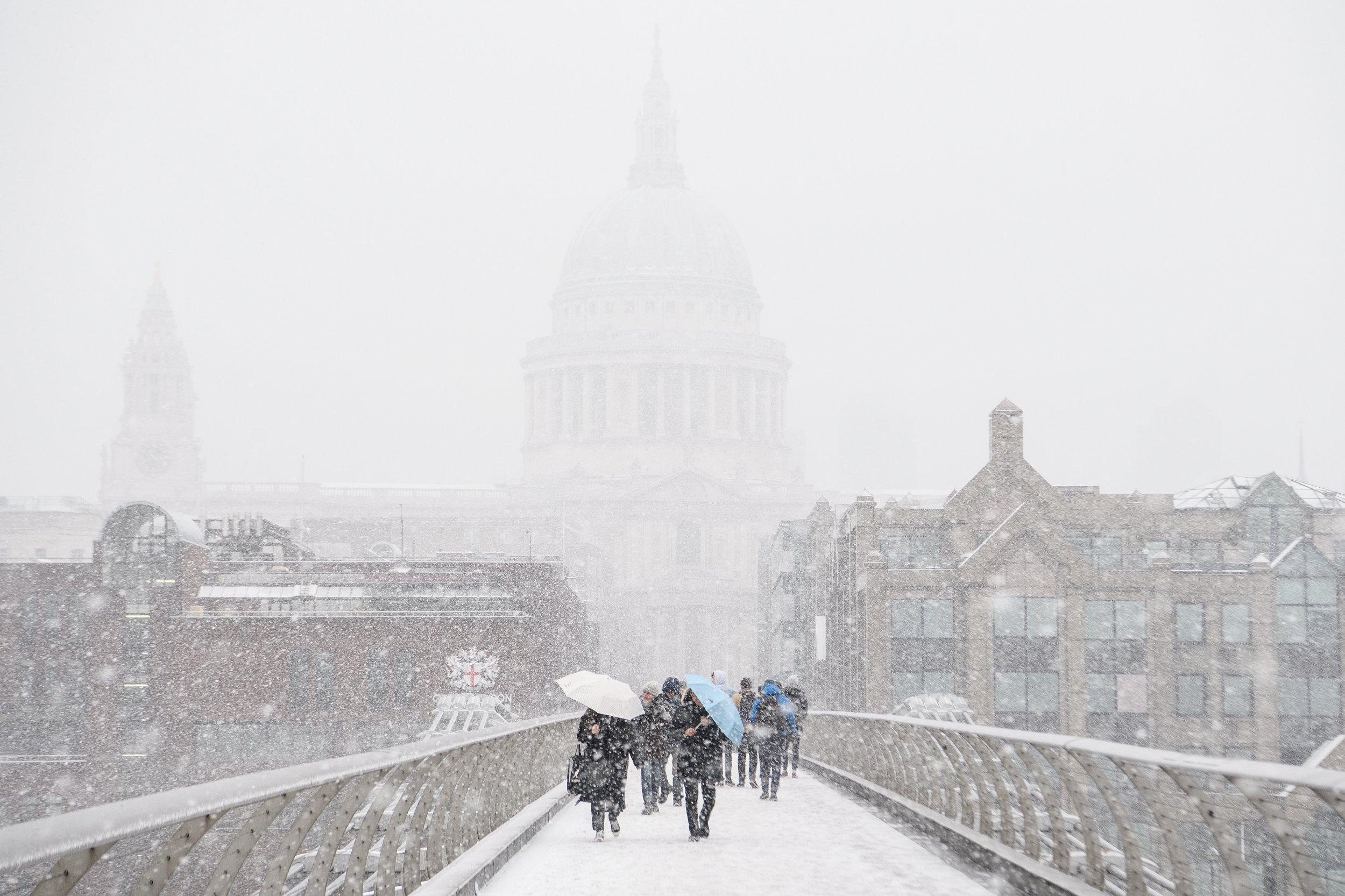 LONDON, UNITED KINGDOM - MARCH 02: Saint Paul's Cathedral is just visible through a blizzard as people cross the River Thames on March 2, 2018 in London, United Kingdom. Weather fronts dubbed Storm Emma and The Beast From The East have combined to create freezing conditions that have bought much of the UK to a standstill. Businesses have closed, some towns are inaccessible and flights have been cancelled costing the British economy millions of pounds. (Photo by Leon Neal/Getty Images)