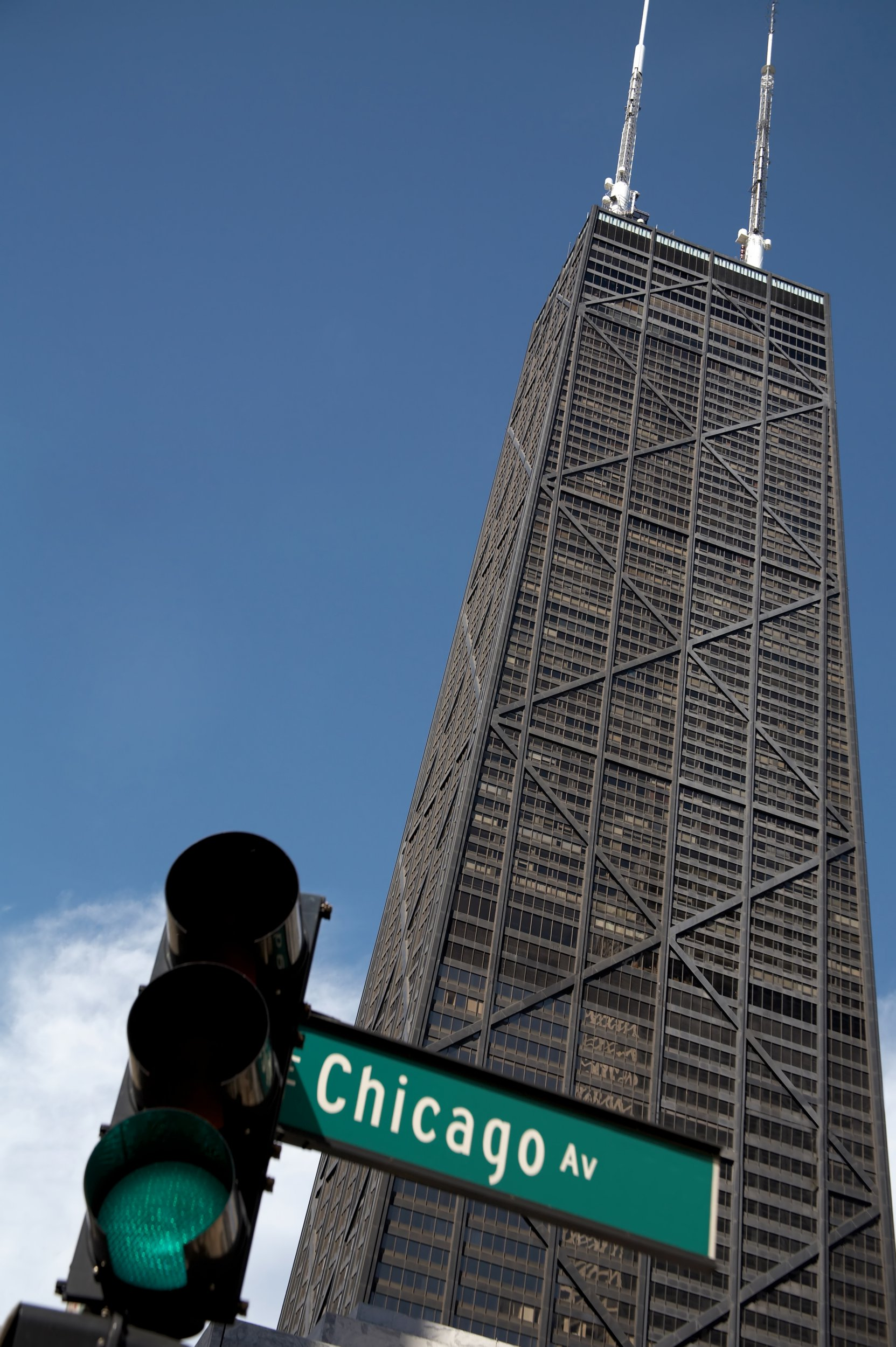 Stock image of a street sign at the intersection of Chicago & Michigan avenues. Focus is on John Hancock building, with signs in foreground slightly out of focus.