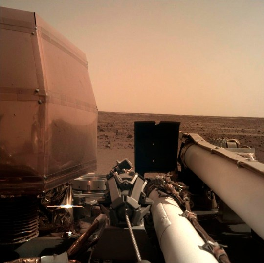 This photo provided by NASA shows an image on Mars that its spacecraft called InSight acquired using its robotic arm-mounted, Instrument Deployment Camera (IDC) after it landed on the planet on Monday, Nov. 26, 2018. The NASA spacecraft designed to drill down into Mars' interior landed on the planet Monday after a perilous, supersonic plunge through its red skies, setting off jubilation among scientists who had waited in white-knuckle suspense for confirmation to arrive across 100 million miles of space. (NASA via AP)
