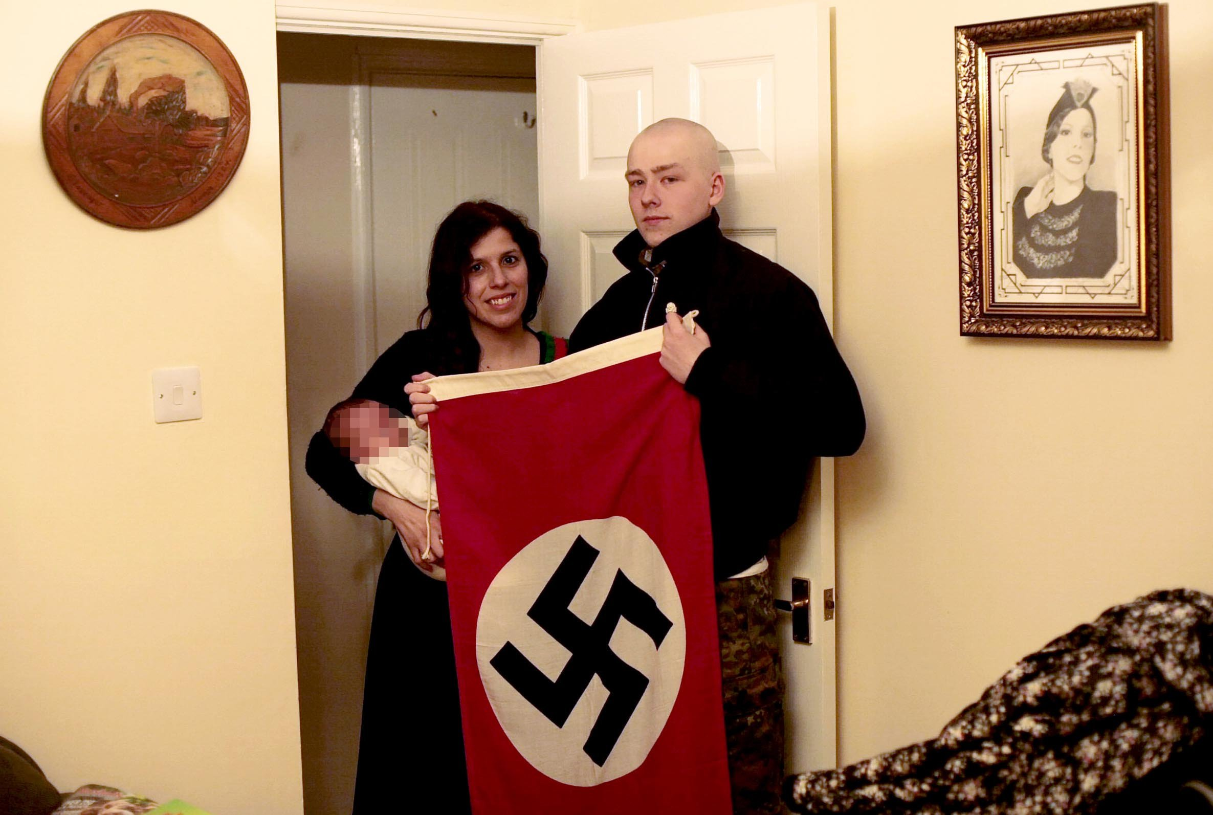 FILE PICTURE - Adam Thomas & Claudia Patatas holding a Swastika flag whilst holding their baby. See SWNS story SWMDnazi. A jury has retired to consider verdicts in the trial of three people accused of being members of a neo-Nazi terrorist group. Adam Thomas, 22, and his 38-year-old partner Claudia Patatas ? who jurors heard named their baby Adolf out of ?admiration? for Hitler ? are accused of membership of the banned group National Action. Warehouse worker Daniel Bogunovic, 27, of Crown Hills Rise, Leicester, is also on trial at Birmingham Crown Court accused of the same charge. During the trial, jurors saw a photograph of former Amazon security guard Thomas in the hooded white robes of the Ku Klux Klan, holding his newborn son. Another image from what prosecutors called the ?Thomas-Patatas family album? showed the smiling couple at home in Waltham Gardens, Banbury, Oxfordshire, with a swastika flag and Patatas holding the baby. The couple allegedly had a poster stuck to their fridge reading ?Britain is ours ? the rest must go?, and a pastry-cutter shaped like a swastika, kept in a kitchen cupboard.