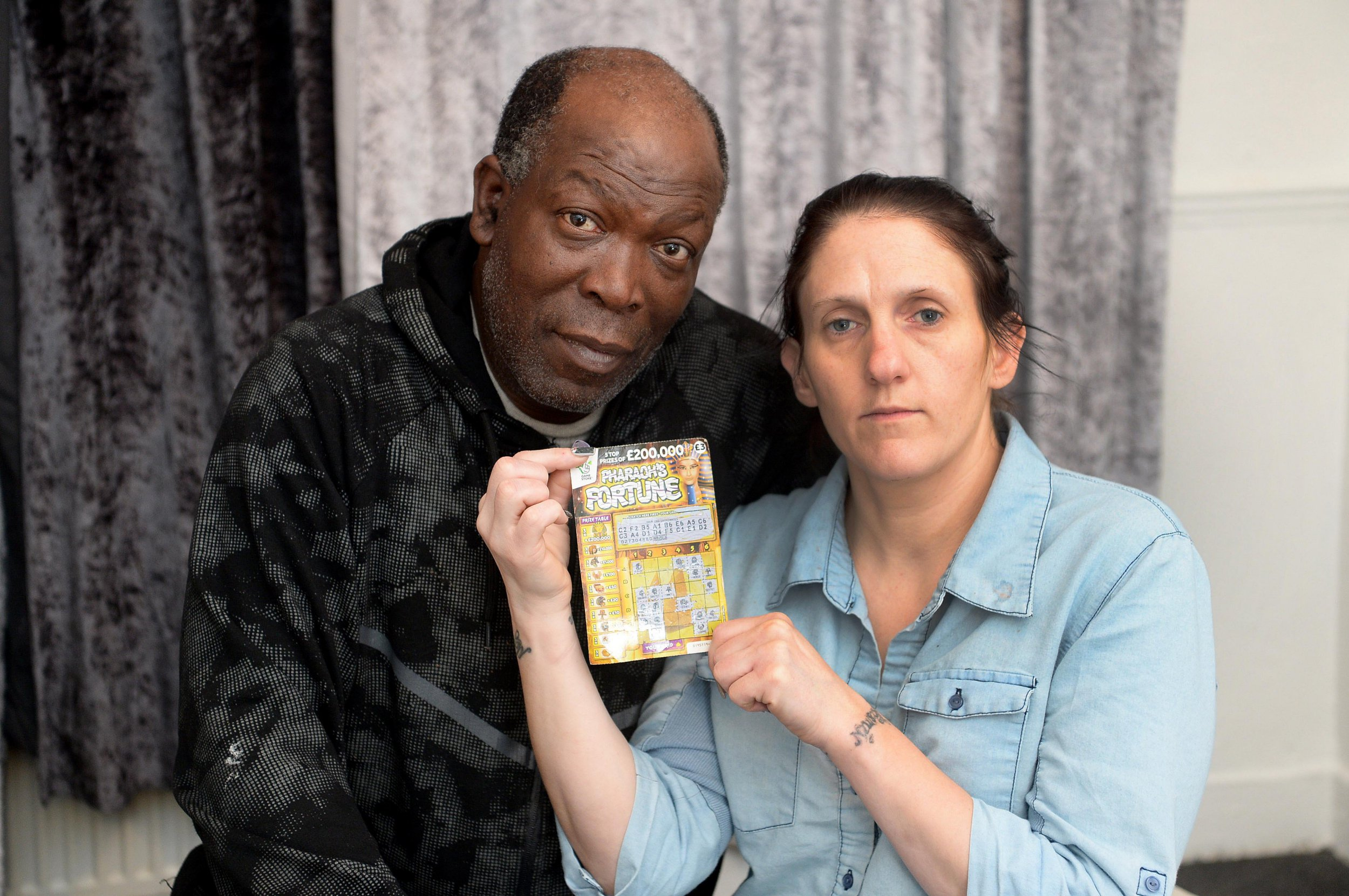 """Eric Walker, 56, with his partner Amanda Emmadi, 36. A National Lottery player insists he has won ?200,000 on a scratchcard - despite Camelot saying the ticket has been doctored. See SWNS story SWLEticket. Eric Walker, 56, was overjoyed when he scratched the ticket and discovered he had won the jackpot prize on the lotto's Pharaoh's Fortune game. But his delight turned to heartbreak when Camelot refused to pay out after seeing a picture of the card and claiming it's doctored. Outraged Eric, a father of four from Sheffield, South Yorks, denies tampering with the ?3 ticket and says it's """"obvious"""" he's won """"fair and square"""". Camelot Group, which is carrying out an investigation, claim it appears a letter F on the card has been changed to an E to turn it into a winning ticket. Eric, who is unemployed and has four children aged between 14 months and nine-years-old, says the money would be """"life changing"""". Eric's card shows that he uncovered three pharaoh symbols on squares D1, E5 and A5, however, the E5 code appears to have been doctored. The F5 square, which the code was originally believed to have been, is also scratched off."""