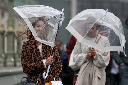 Pedestrians struggle to shelter from the rain and wind as they walk across Westminster Bridge in London on November 28, 2018. - Britain's Met Office issued warnings for high winds as Storm Dianna, named by the Portuguese authorities, started to impact Britain. (Photo by Daniel LEAL-OLIVAS / AFP) (Photo credit should read DANIEL LEAL-OLIVAS/AFP/Getty Images)