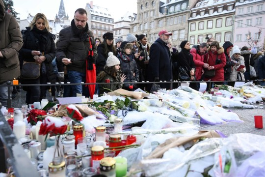 People light-up candles and deposit flowers during a gathering around a makeshift memorial at Place Kleber, in Strasbourg, on December 16, 2018 to pay a tribute to the victims of Strasbourg's attack. - Four people were killed and 12 wounded when a lone gunman, identified as Cherif Chekatt, 29, opened fire on shoppers near the Christmas market, on December 11, 2018, according to French officials. (Photo by SEBASTIEN BOZON / AFP)SEBASTIEN BOZON/AFP/Getty Images