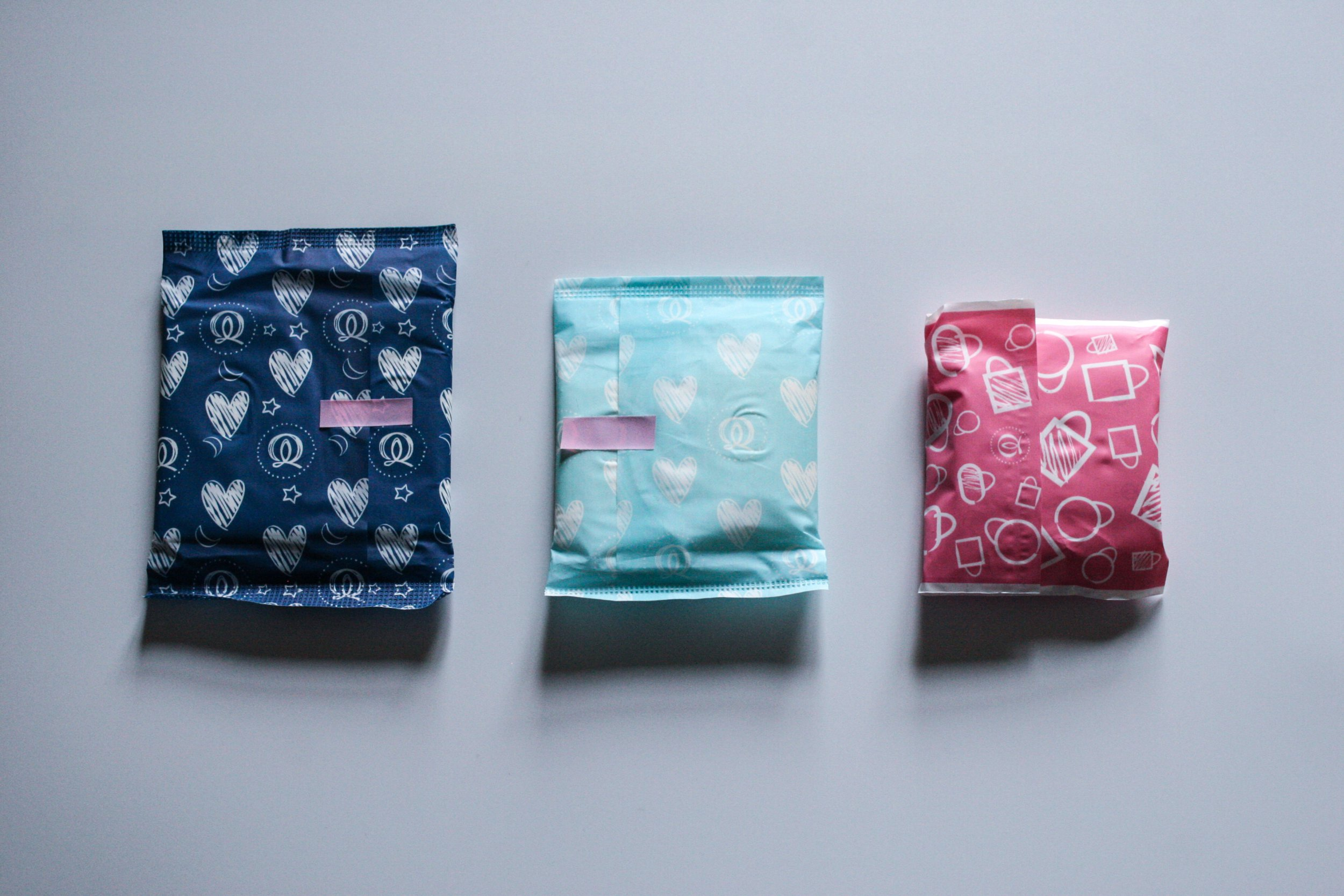 Set of three sanitary towels / panty liners in different sizes wrapped in different colours.