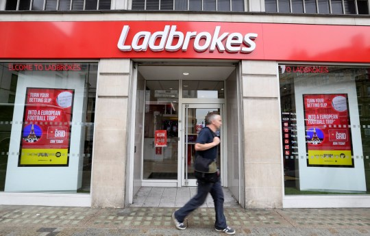 A pedestrian passes a branch of Ladbrokes Plc bookmakers, in London, U.K., on Friday, July 24, 2015. Ladbrokes Plc agreed to buy Coral Group in a share-exchange deal to create the U.K.'s biggest betting-shop chain and fight back against a tide of online competition. Photographer: Chris Ratcliffe/Bloomberg via Getty Images