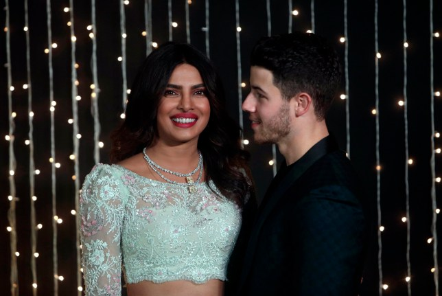 Bollywood actress Priyanka Chopra and musician Nick Jonas pose for photographs at their wedding reception in Mumbai, India, Thursday, Dec 20, 2018. (AP Photo/Rajanish Kakade)