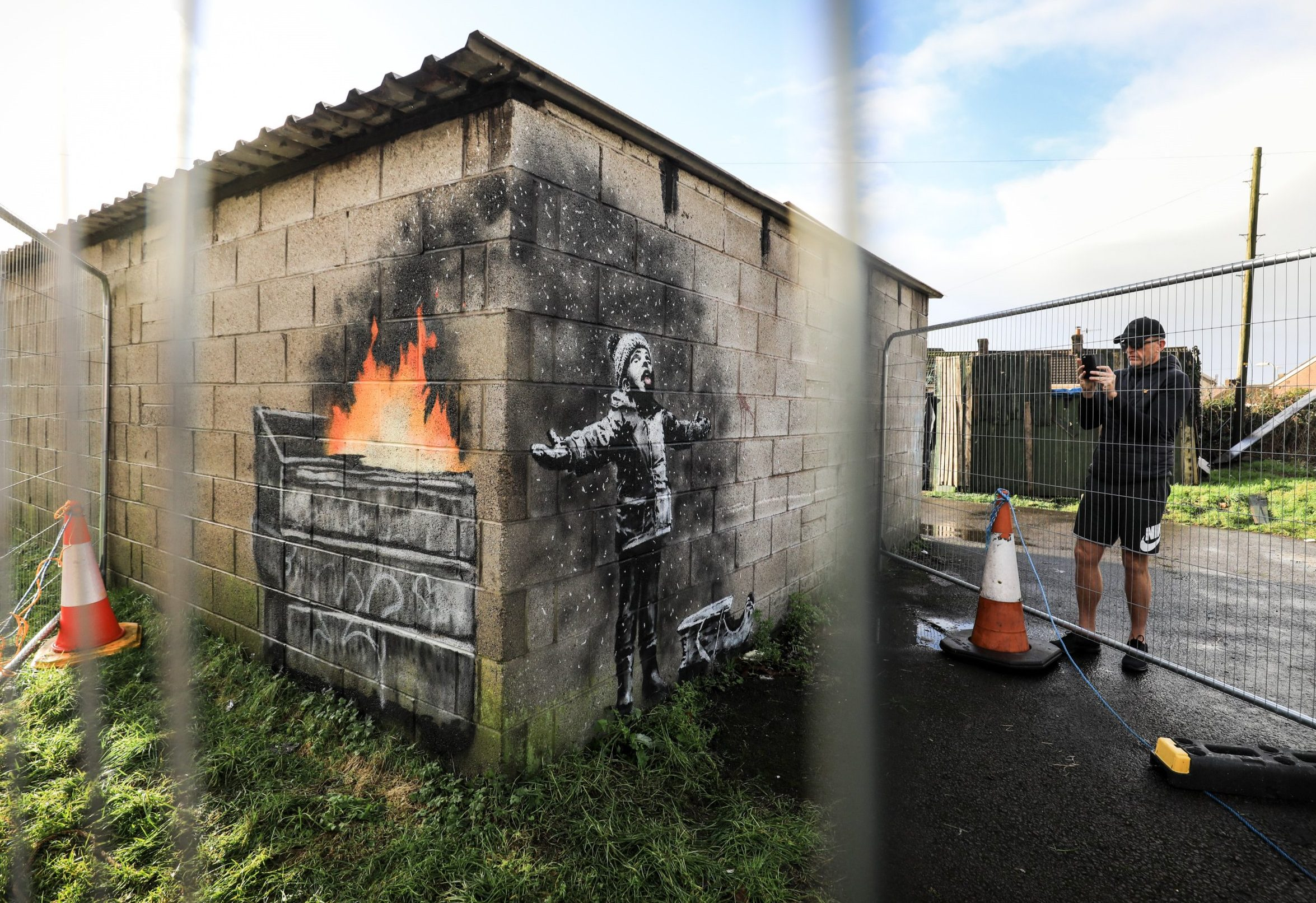 """PORT TALBOT, WALES - DECEMBER 20: People gather around fences that have been erected to protect the latest piece of artwork by the underground guerrilla artist Banksy on December 20, 2018 in Port Talbot, Wales. The British graffiti artist who keeps his identity a secret, confirmed yesterday that the artwork was his using his verified Instagram account to announce """"Season's greetings"""" with a video of the artwork in Port Talbot. (Photo by Matt Cardy/Getty Images) *** BESTPIX ***"""