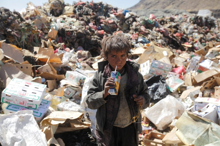 A boy drinks expired juice on a pile of rubbish at landfill site on the outskirts of Sanaa, Yemen November 16, 2016. REUTERS/Mohamed al-Sayaghi - D1BEUNEWHQAA