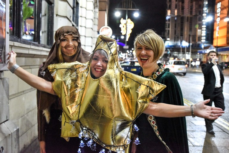Pic by Michael Scott/Caters News - (PICTURED: The Nativity has come to Broad Street in Birmingham as 3 girls dressed up as Joseph, a star and a Wise man as they joined other revellers who celebrated Mad Friday. Pic taken: 22/12/2018) - Thousands of festive revellers took to Broad Street in Birmingham as the last Friday before Christmas took hold. Also known as Mad Friday or Black Eye Friday due to fighting, many use the evening on their last work night before Christmas. The evening saw a woman being carted into an ambulance after being found lying next to a parked car, a couple of girls had won a huge pink unicorn for a club night called Bongo Bingo, Several partygoers were also seen being sick as friends comforted them. Love was in they are as many had an early morning snog. Police and paramedics were also out in force to make sure everyone was okay, and to top the night off a West Midlands bus driver even wore a Santa suit as he drove the night bus through the nightclub strip which brought smiles to peoples faces. ENDS