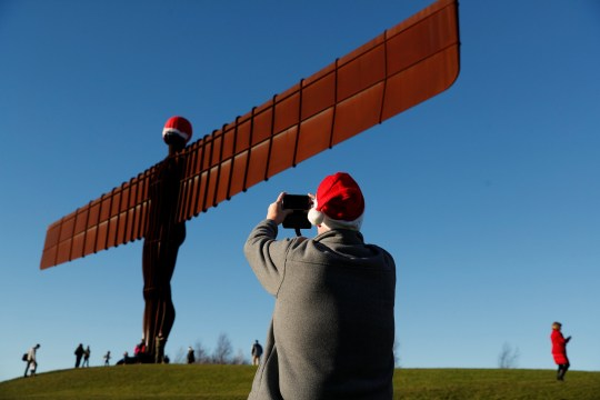 6813c89885198 Passerby takes pictures of the Angel of the North statue adorned with Sant  Claus  hat