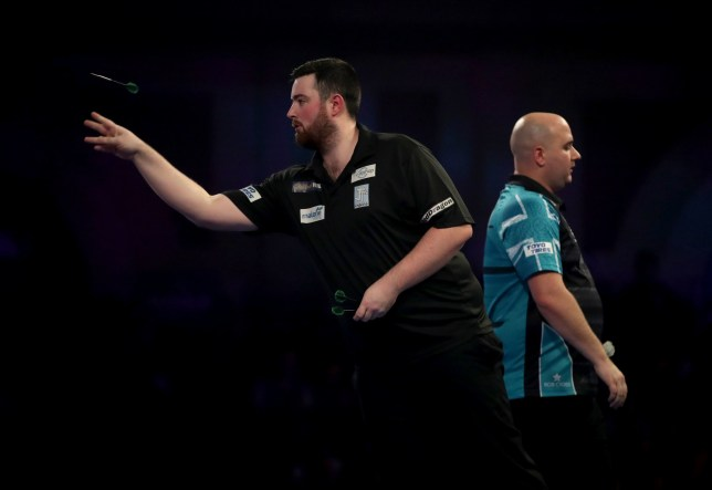 Luke Humphries (left) defeats Rob Cross (right) during day thirteen of the William Hill World Darts Championships at Alexandra Palace, London. PRESS ASSOCIATION Photo. Picture date: Friday December 28, 2018. See PA story DARTS World. Photo credit should read: Adam Davy/PA Wire