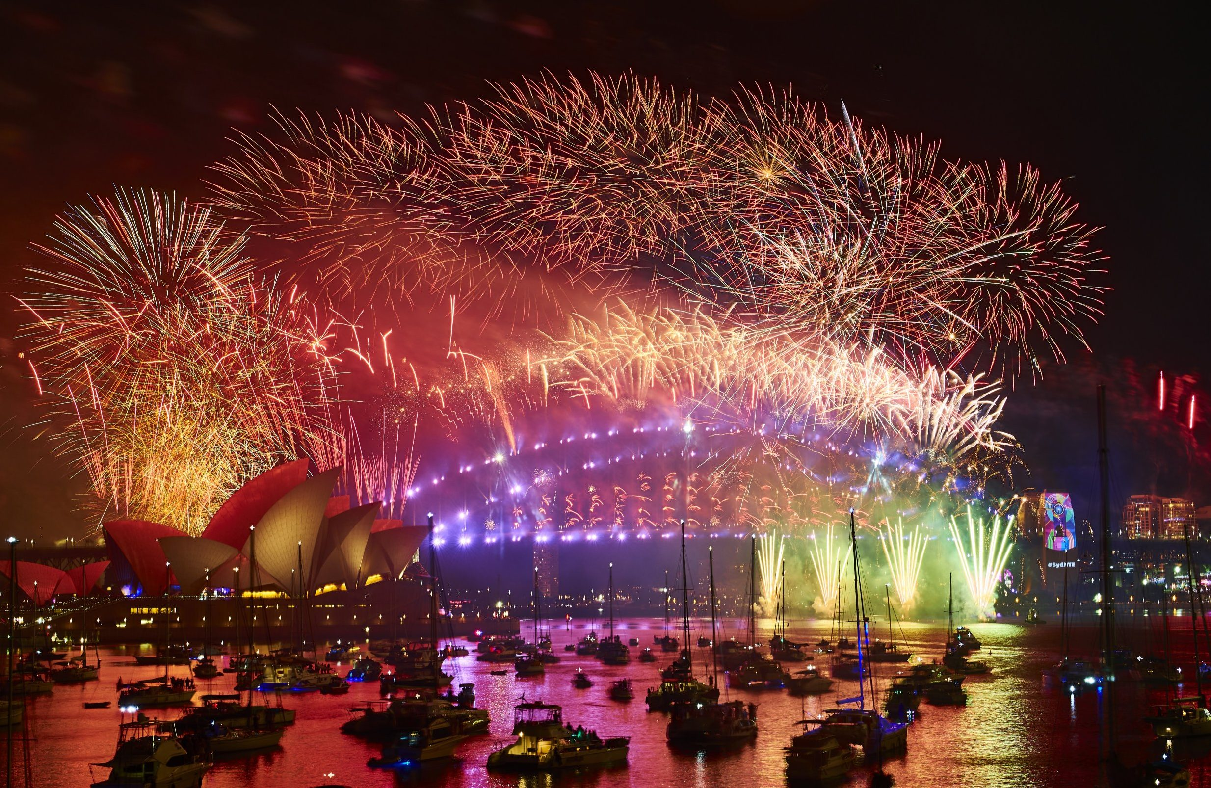 SYDNEY, AUSTRALIA - JANUARY 01: Fireworks explode over the Sydney Harbour Bridge and Sydney Opera House during the midnight display on New Year's Eve on Sydney Harbour on January 1, 2019 in Sydney, Australia. (Photo by Brett Hemmings\City of Sydney/Getty Images)