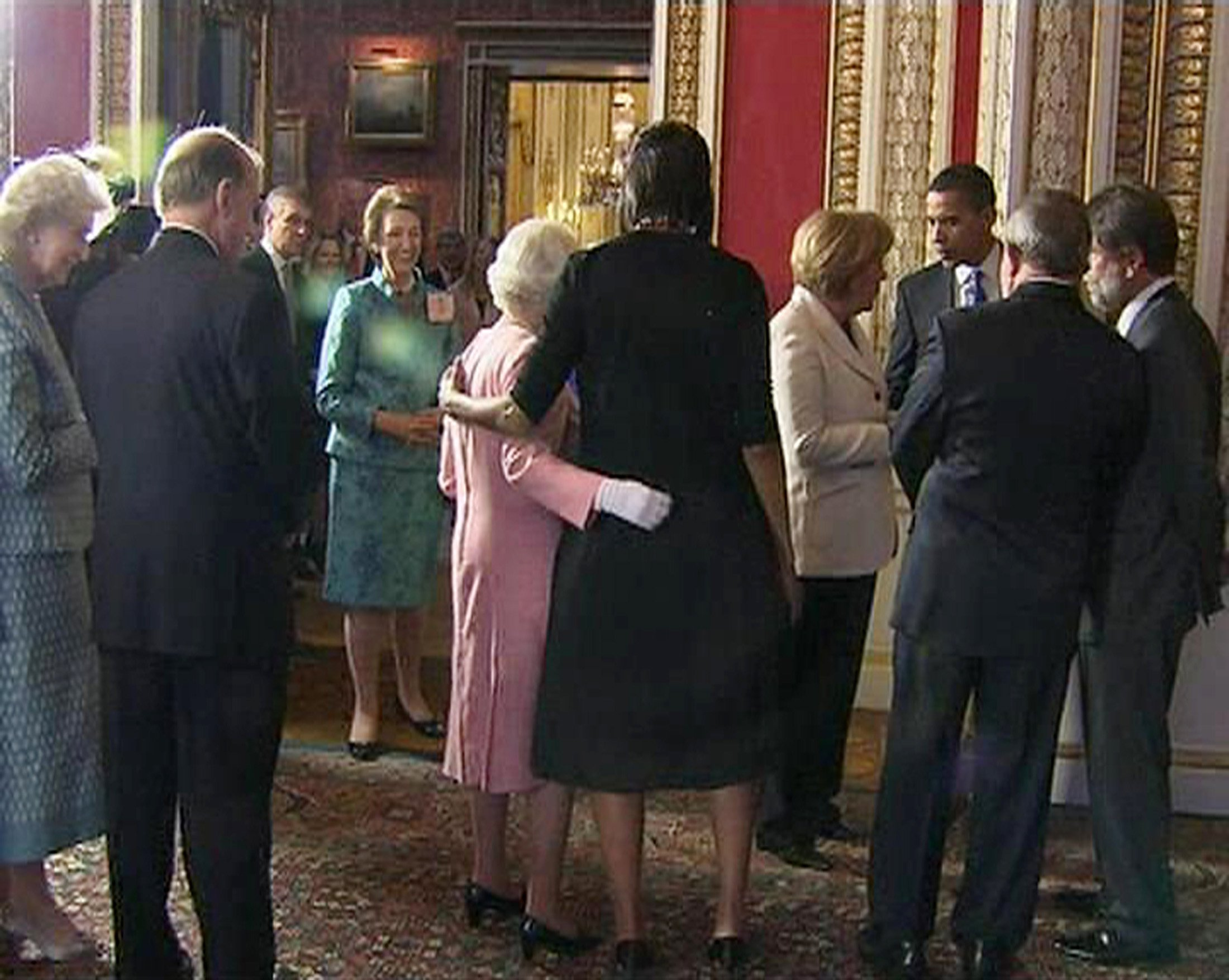 A video grab from television footage shows U.S. first lady Michelle Obama (C) standing with Britain's Queen Elizabeth during a reception for G20 leaders at Buckingham Palace in London April 1, 2009. World leaders arrived in London on Wednesday ahead of a G20 summit meeting under intense pressure to produce a morale-boosting response to the worst economic downturn since the 1930s. REUTERS/POOL via Reuters Tv (BRITAIN BUSINESS POLITICS ROYALS) FOR EDITORIAL USE ONLY. NOT FOR SALE FOR MARKETING OR ADVERTISING CAMPAIGNS - GM1E5421E0Q01