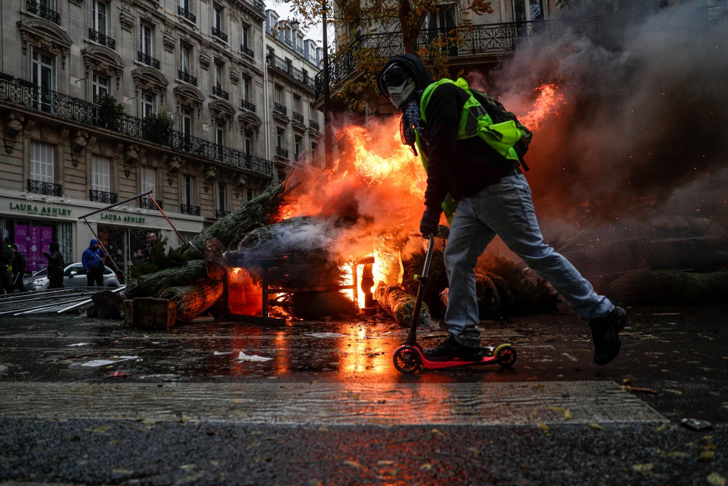 A demonstrator rides past a fire during a protest of Yellow vests (Gilets jaunes) against rising oil prices and living costs, on December 1, 2018 in Paris. - Speaking at the Paris police's command centre, French Prime Minister said 36,000 people were protesting across France, including 5,500 in the capital for this 3rd nationwide day of blockade ands demos. (Photo by Geoffroy VAN DER HASSELT / AFP)GEOFFROY VAN DER HASSELT/AFP/Getty Images