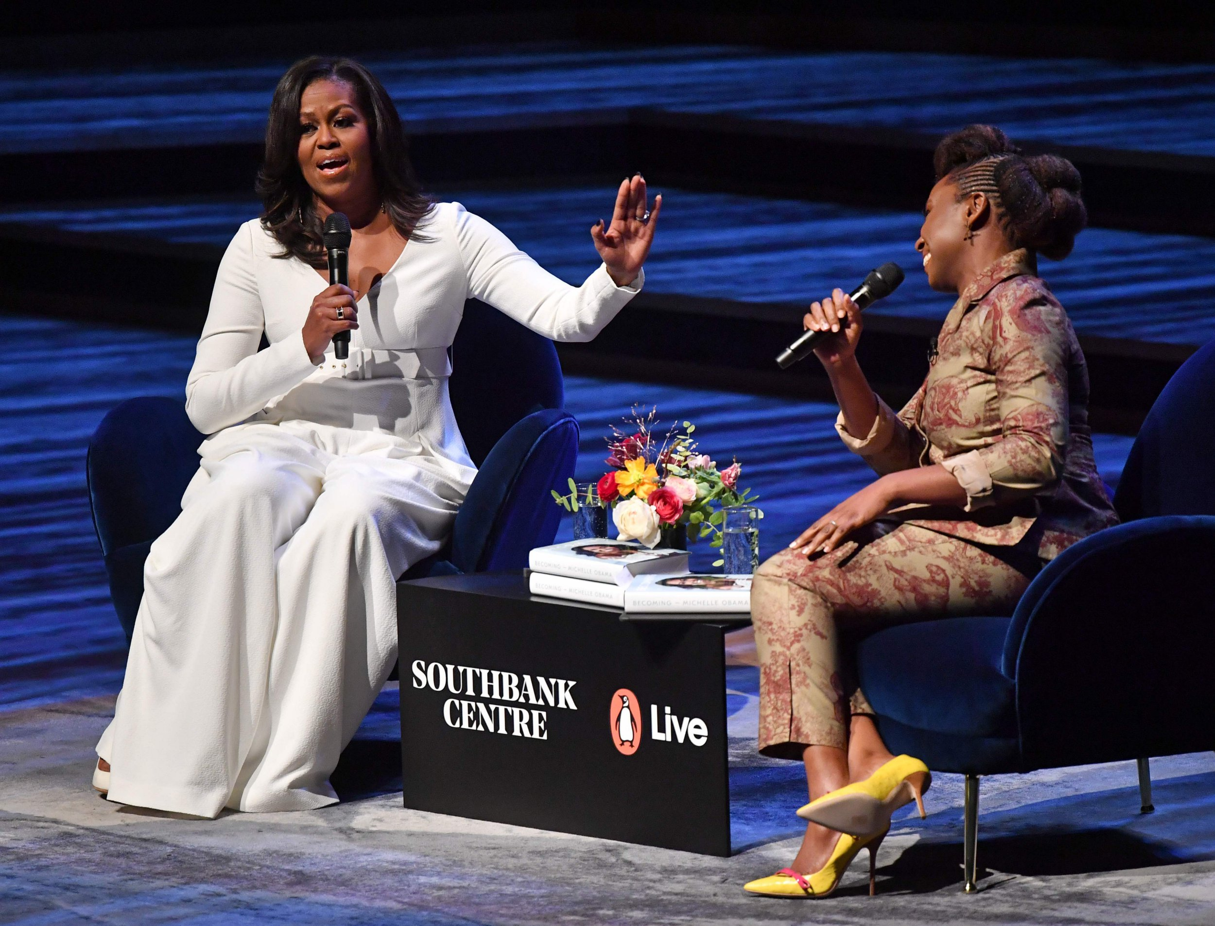 """Former US first lady Michelle Obama (L) speaks with Nigerian novelist Chimamanda Ngozi Adichie (R) at the Royal Festival Hall in London on December 3, 2018, during a tour to promote her memoir, """"Becoming"""". - Former US first lady Michelle Obama's book, """"Becoming,"""" sold more than two million copies in North America in its first 15 days. She said Sunday she was canceling book tour visits to Paris and Berlin to attend the funeral of former president George H.W. Bush, who died Friday aged 94. (Photo by Ben STANSALL / AFP)BEN STANSALL/AFP/Getty Images"""