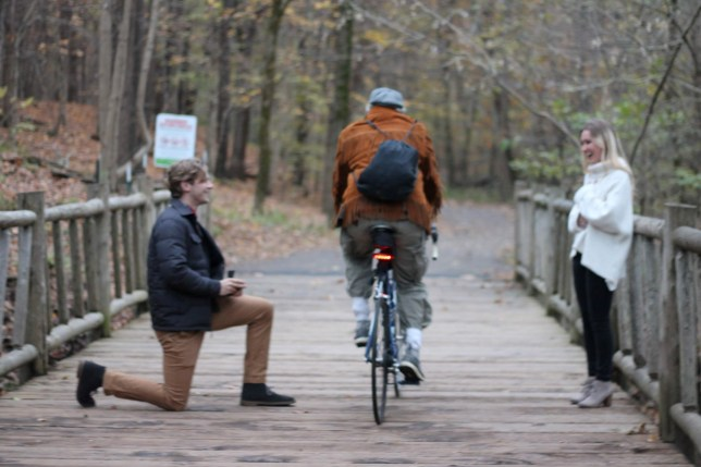 """This is the moment a couple?s intimate marriage proposal was INTERRUPTED by a speeding cyclist after three months of planning. See SWNS story SWNYpropose; Blake Martin, 25, was horrified when a cyclist bounded between he and his girlfriend Shannon Keene, 24, just after he had gone down on one knee to propose. PHD student Blake had just asked the all important question when ?an orange blur? whizzed across the wooden bridge in Cherokee Park in Louisville, Kentucky on November 9. The couple were stunned as the moment-wrecking cyclist apologized quickly before continuing on his way. The funny moment was captured on camera photographer Christine Calacsan, a friend of the couple who had been roped into Blake?s plans from the beginning. Shannon said: """"One of my law school friends has taken photos of us in the past and Blake reached out to her and asked her if she could send me a message, pretending she wanted to test out her new lens."""