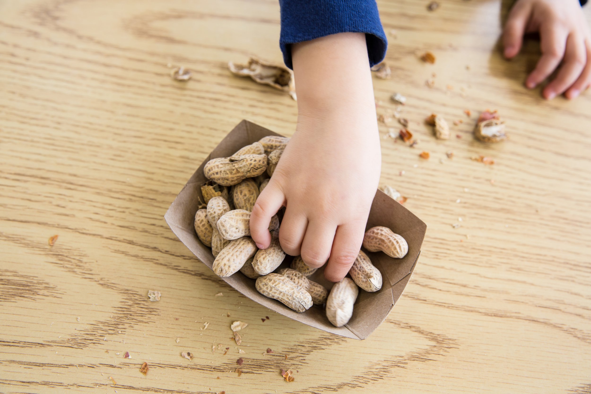 Unrecognizable little boy sits at a table eating peanuts