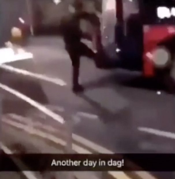 A man kicks the glass in the door a London bus in Dagenham, December 2018. A SHOCKING video has surfaced of a man violently kicking and smashing TWO bus windows following an argument with the driver in Dagenham, East London. In the astonishing clip, the male screams at the driver to move his bus. When the driver refuses to move, the furious man suddenly kicks one of the bus??? front doors and the glass shatters to the ground. Bystanders scream as the enraged man swears and then kicks ANOTHER one of bus front glass doors so that it crashes on the pavement. The video was originally posted on Snapchat by a user who goes by the username ???Smallz??? and the footage has since been shared across social media. The incident took place on the corner of Holgate Road and Heathway in Dagenham, East London and the clip is believed to have been filmed recently. ... SEE COPY AND VID ... PIC BY NEWS DOG MEDIA ... 0121 517 0019