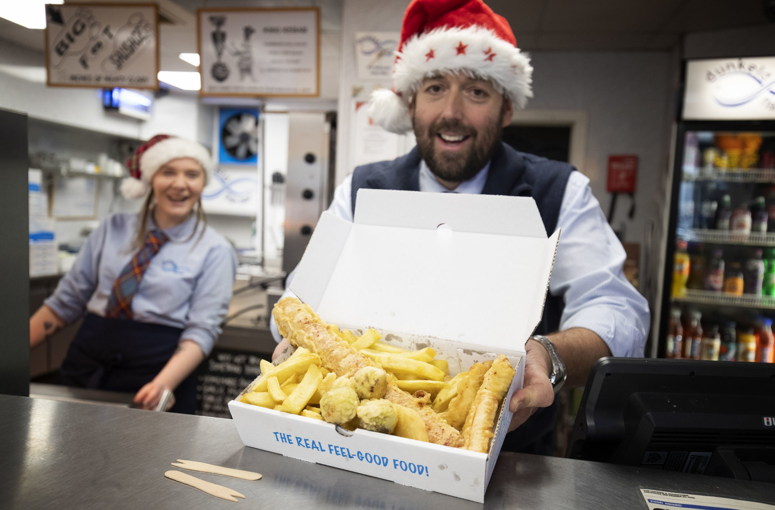Chelsea McGowan and owner Scott Davie serve up a deep-fried Christmas dinner, complete with turkey, parsnips and brussels sprouts, which is on the menu during the festive season at Dunkeld Fish Bar in Dunkeld, Perthshire. PRESS ASSOCIATION Photo. Picture date: Sunday December 9, 2018. Photo credit should read: Jane Barlow/PA Wire