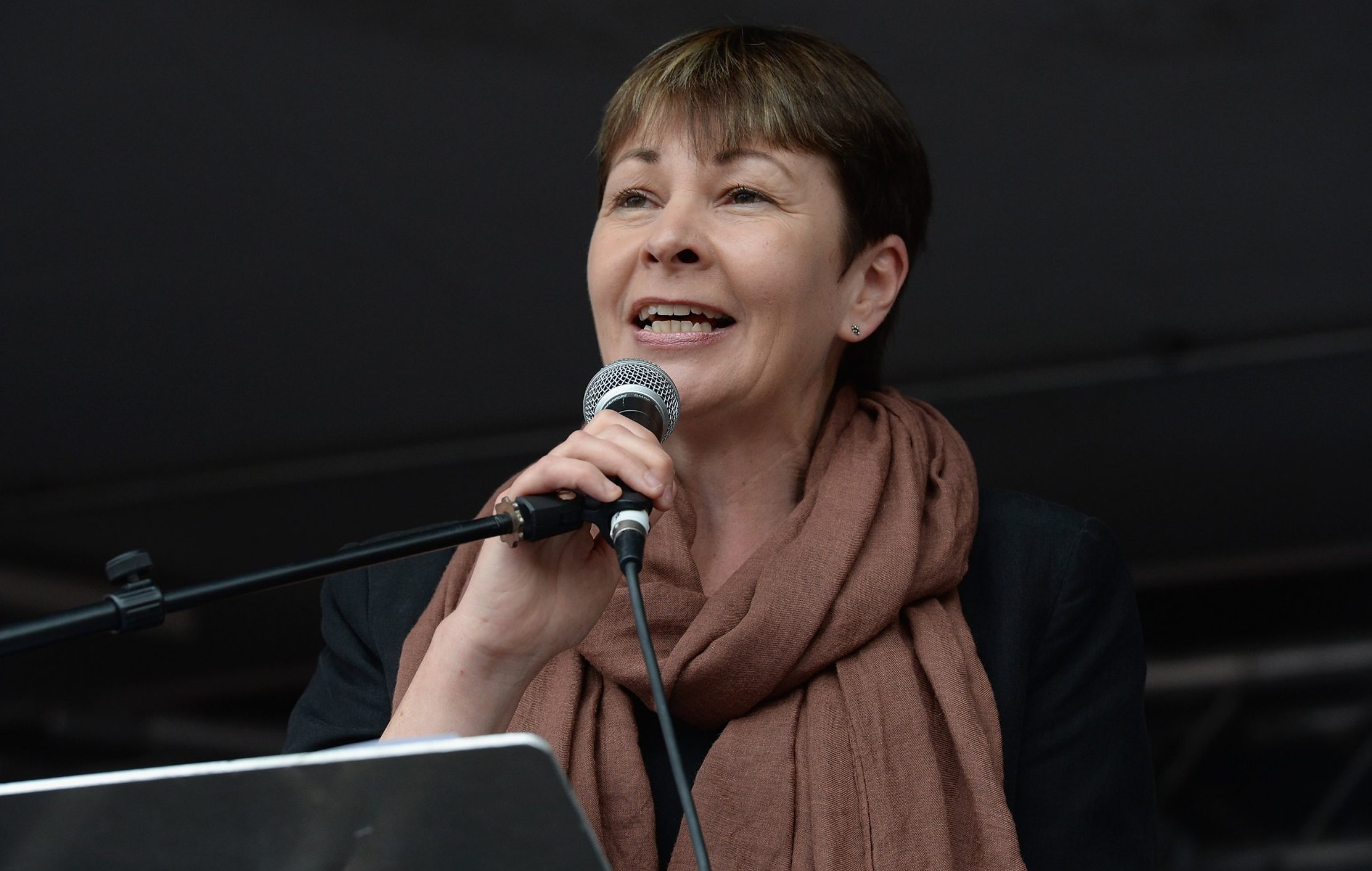 LONDON, ENGLAND - JUNE 20: Green Party MP for Birghton and Hove, Caroline Lucas, speaks to thousands of demonstrators gathered in Parliament Square to protest against austerity and spending cuts on June 20, 2015 in London, England. Thousands of people gathered to march from the City of London to Westminster, where they listened to addresses from singer Charlotte Church and comedian Russell Brand as well as Len McCluskey, general secretary of Unite and Sinn Fein's Martin McGuinness. (Photo by Mary Turner/Getty Images)