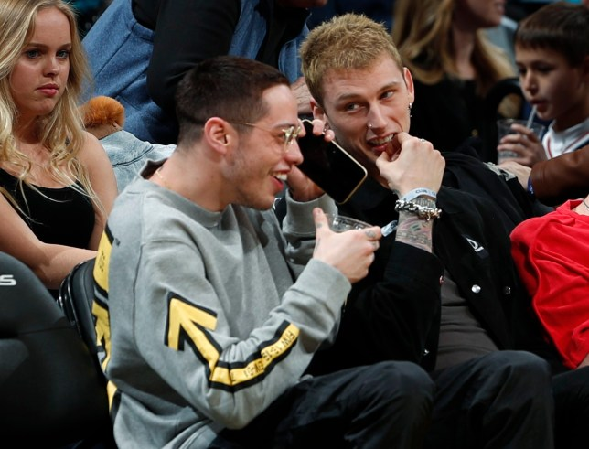 Comedian Pete Davidson, front left, jokes with rapper Machine Gun Kelly as they sit courtside to watch the Denver Nuggets host the Charlotte Hornets in the second half of an NBA basketball game Saturday, Jan. 5, 2019, in Denver. (AP Photo/David Zalubowski)