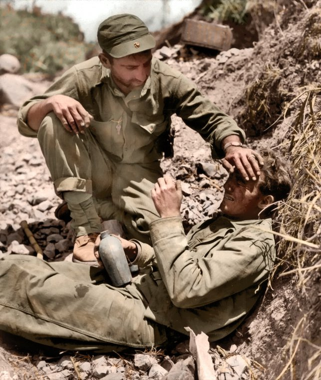 """Marine comforts a brother Leatherneck who broke down after witnessing the death of a buddy on an Okinawa hillside, 1945 THE BRUTAL reality of World War Two has been brought to life in a series of stunning yet emotional colourised images from one of the world???s most devastating conflicts. Striking shots show Sgt Jake McNiece of the 101st Airborne Division, ready to drop into Normandy, a Marine comforting a brother who broke down after witnessing the death of a friend and American troops walk down a war ravaged street, Messina, Sicily. Other vivid colour pictures show U.S Army military policemen toasting bread over molten lava from Mt Vesuvius after its eruption, Guardsmen of 3rd Irish Guards in a Lloyd carrier, wrapped up against the clouds of dust, during Operation ???Goodwood???, and the crew of the B-17 Flying Fortress """"Memphis Belle"""" is shown at an air base in England after completing 25 missions over enemy territory. The original black and white photographs were painstakingly colourised by design engineer Paul Reynolds (48), from Birmingham, UK. Paul Reynolds / mediadrumworld.com"""