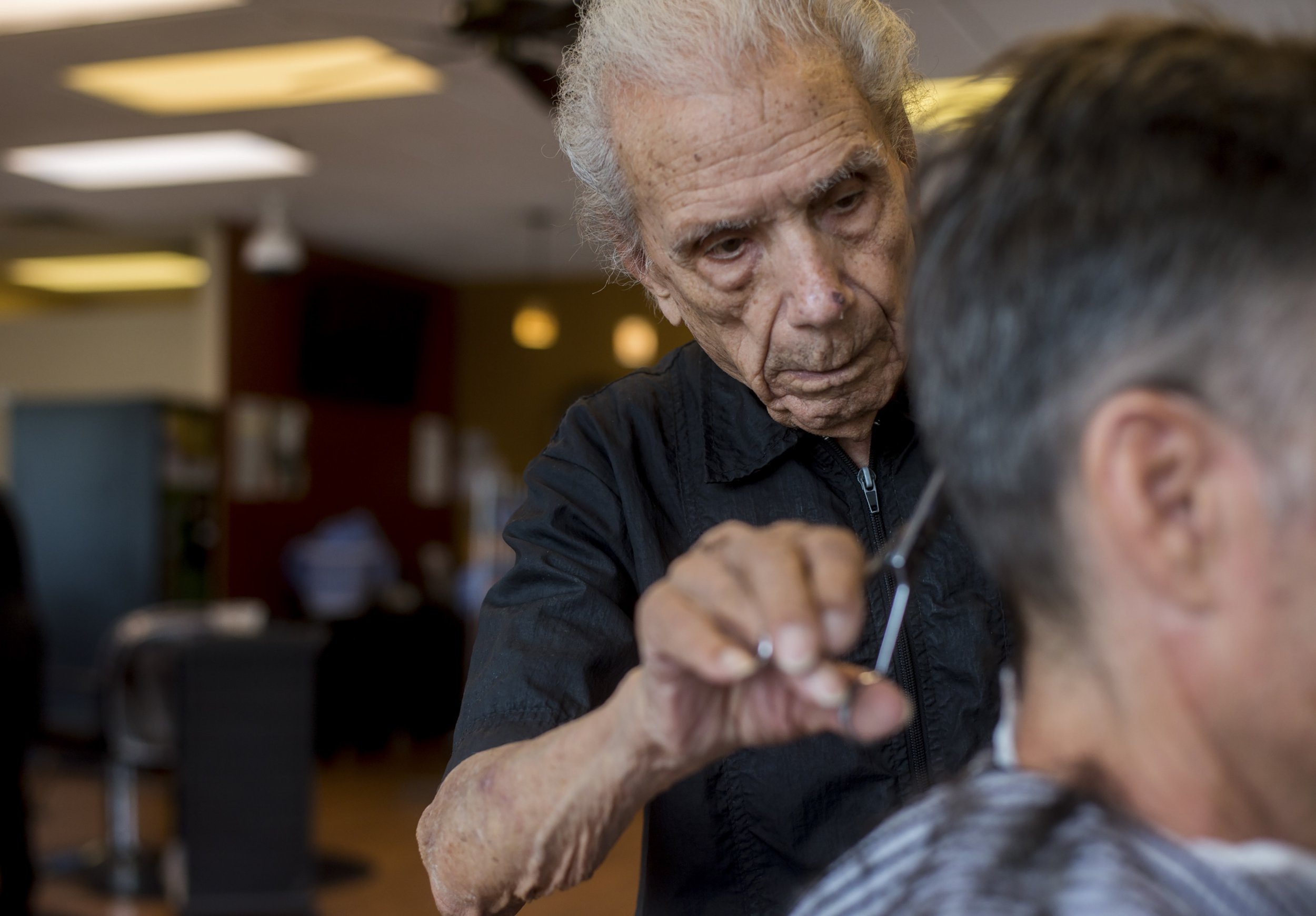 Anthony Mancinelli trims the hair of a customer at Fantastic Cuts, a hair salon in New Windsor, in upstate New York, Sept. 27, 2018. Mancinelli, 107, who began cutting hair when Warren Harding was president, has been recognised by Guinness World Records as the oldest working barber. (Andrew Seng/The New York Times) / Redux / eyevine Please agree fees before use. SPECIAL RATES MAY APPLY. For further information please contact eyevine tel: +44 (0) 20 8709 8709 e-mail: info@eyevine.com www.eyevine.com