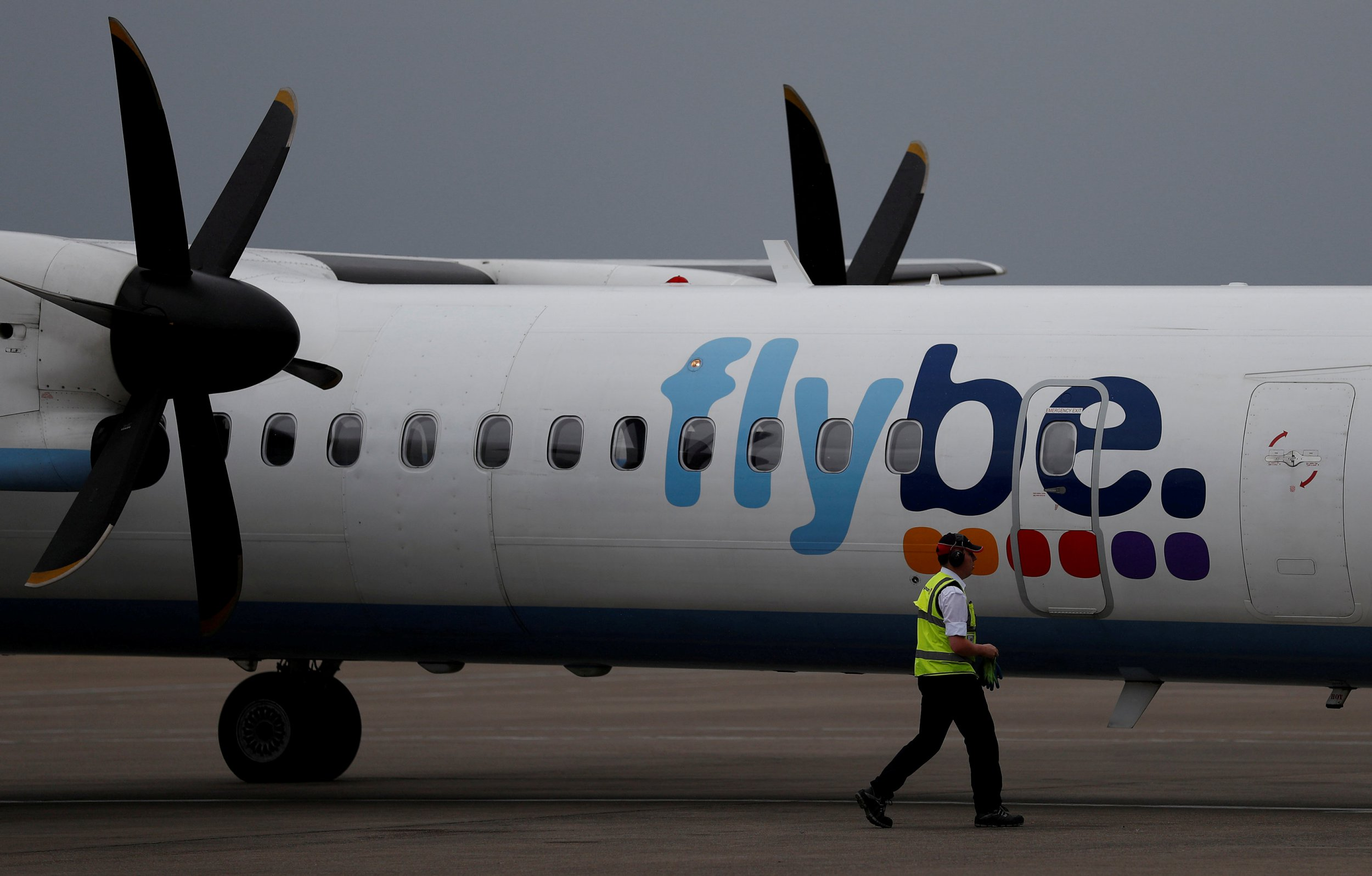 FILE PHOTO: An airport worker examines a flybe aircraft before it takes off from Liverpool John Lennon Airport in Liverpool northern England, May 19 , 2016. REUTERS/Phil Noble/File Photo