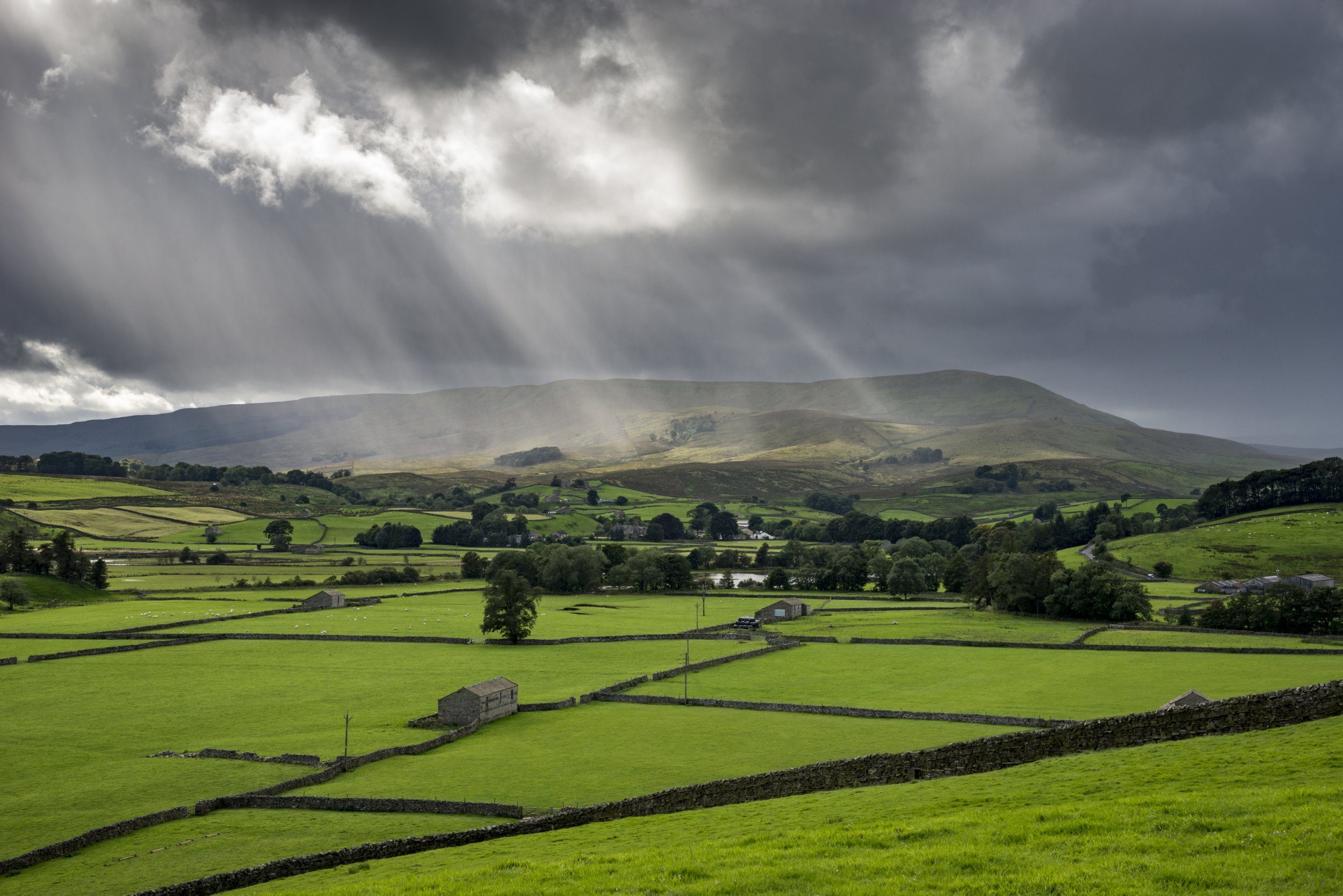 A dramatic day of changeable weather in the Yorkshire Dales in September. Sunbeams and heavy rain over green fields near Hawes.