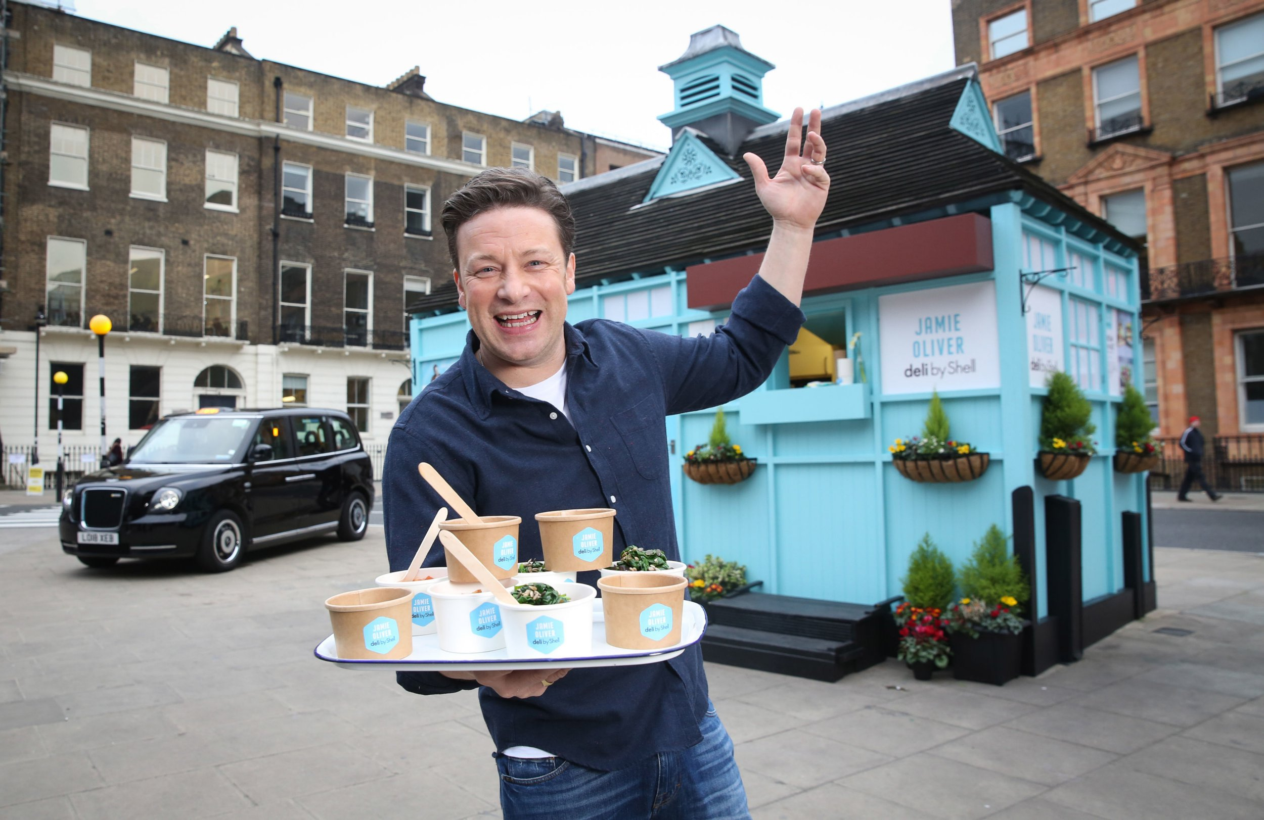 EDITORIAL USE ONLY Jamie Oliver hands out food at his bitesize pop-up cafe at a traditional cabmen's shelter in Russell Square, London, to announce the launch of Jamie Oliver deli by Shell. PRESS ASSOCIATION Photo. Picture date: Tuesday January 15, 2019. The new menu will include such snacks as Superfood Red Fruit Porridge Hot Pot, Egg, Bean & Bacon Hot Pot, Mediterranean roasted veggie & ricotta wrap, a smoked cheese and slaw spicy chipotle chicken sandwich as well as a new kids' meal box which will feature a sandwich, fruit, vegetables and a dip. The 80 new products will be available at over 500 of Shell's service stations across the UK from January 31st. Photo credit should read: Matt Alexander/PA Wire