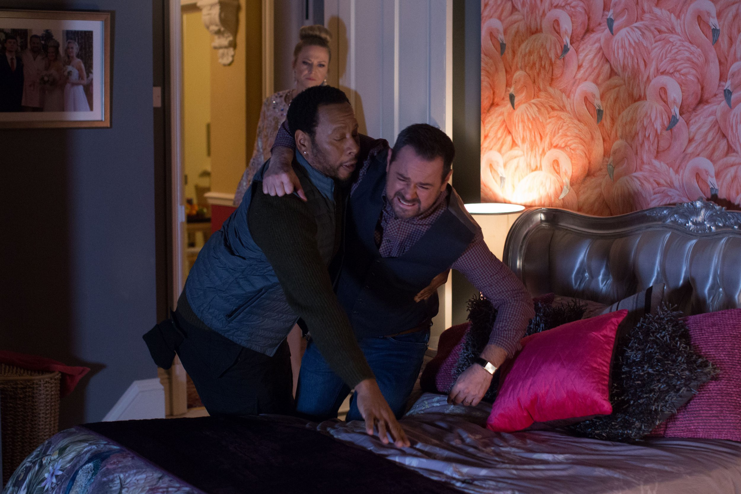 WARNING: Embargoed for publication until 00:00:01 on 22/01/2019 - Programme Name: EastEnders - January - March 2019 - TX: 29/01/2019 - Episode: EastEnders - January - March - 2019 - 5859 (No. 5859) - Picture Shows: *STRICTLY NOT FOR PUBLICATION UNTIL 00:01HRS TUESDAY 22nd JANUARY 2019* Mitch helps an injured Mick to bed Mitch Baker (ROGER GRIFFITHS), Linda Carter (KELLIE BRIGHT), Mick Carter (DANNY DYER) - (C) BBC - Photographer: Jack Barnes