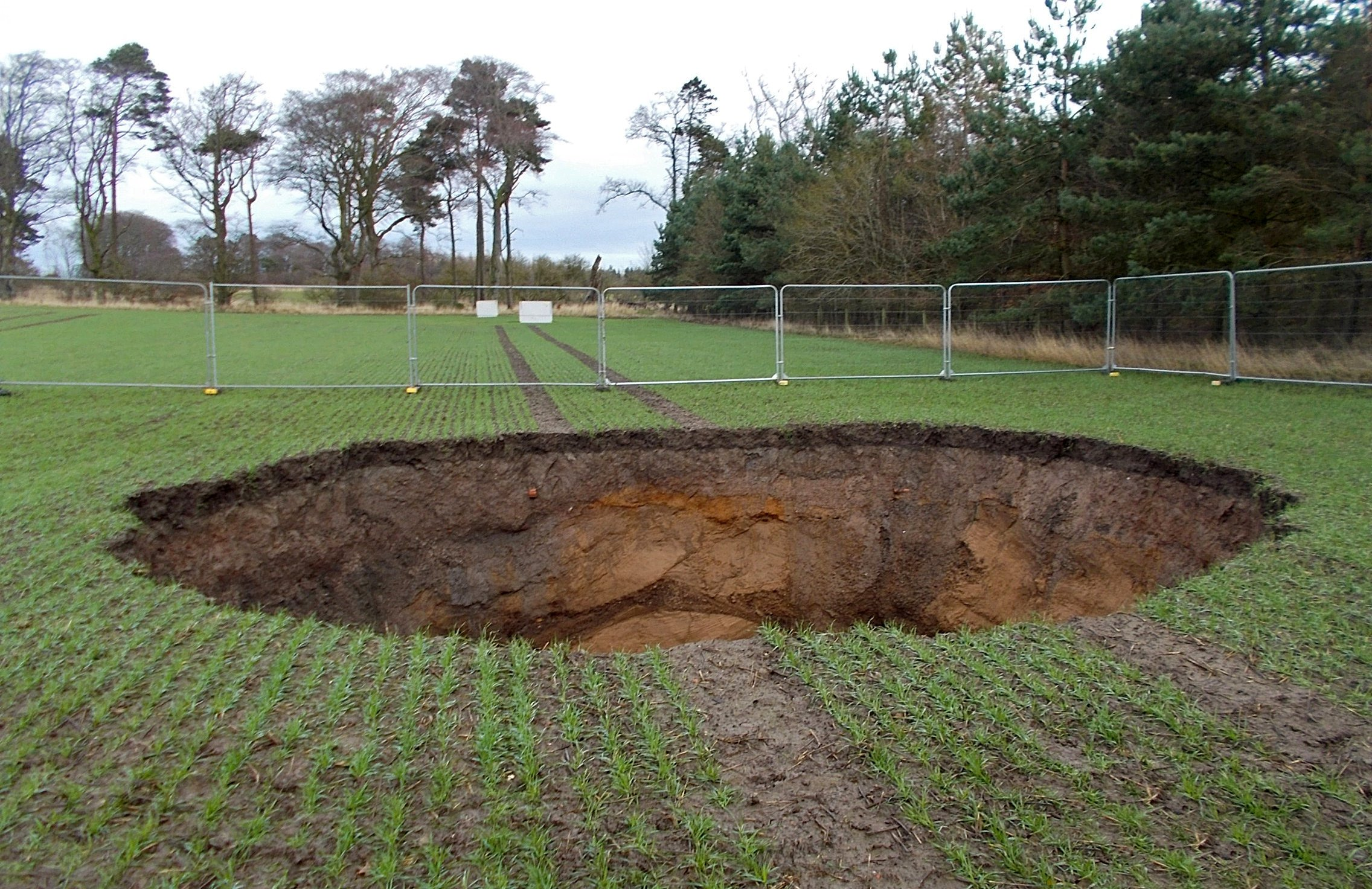 """A sinkhole 10m wide and 6m deep has opened up in a field in Midlothian. See SWNS story SWSChole; Shocking picture shows a 6m deep hole in a wheat field spotted by a landowner. The public safety and subsidence team at the Coal Authority were alerted to a 10m wide hole in a field in Midlothian. The safety team say the hole has been made safe while they investigate the cause by checking geological and mining plans. James Hammond, regional project manager for the public safety and subsidence team at the Coal Authority, said: """"In December 2018, we received a report of a hole in a field in North Midlothian."""