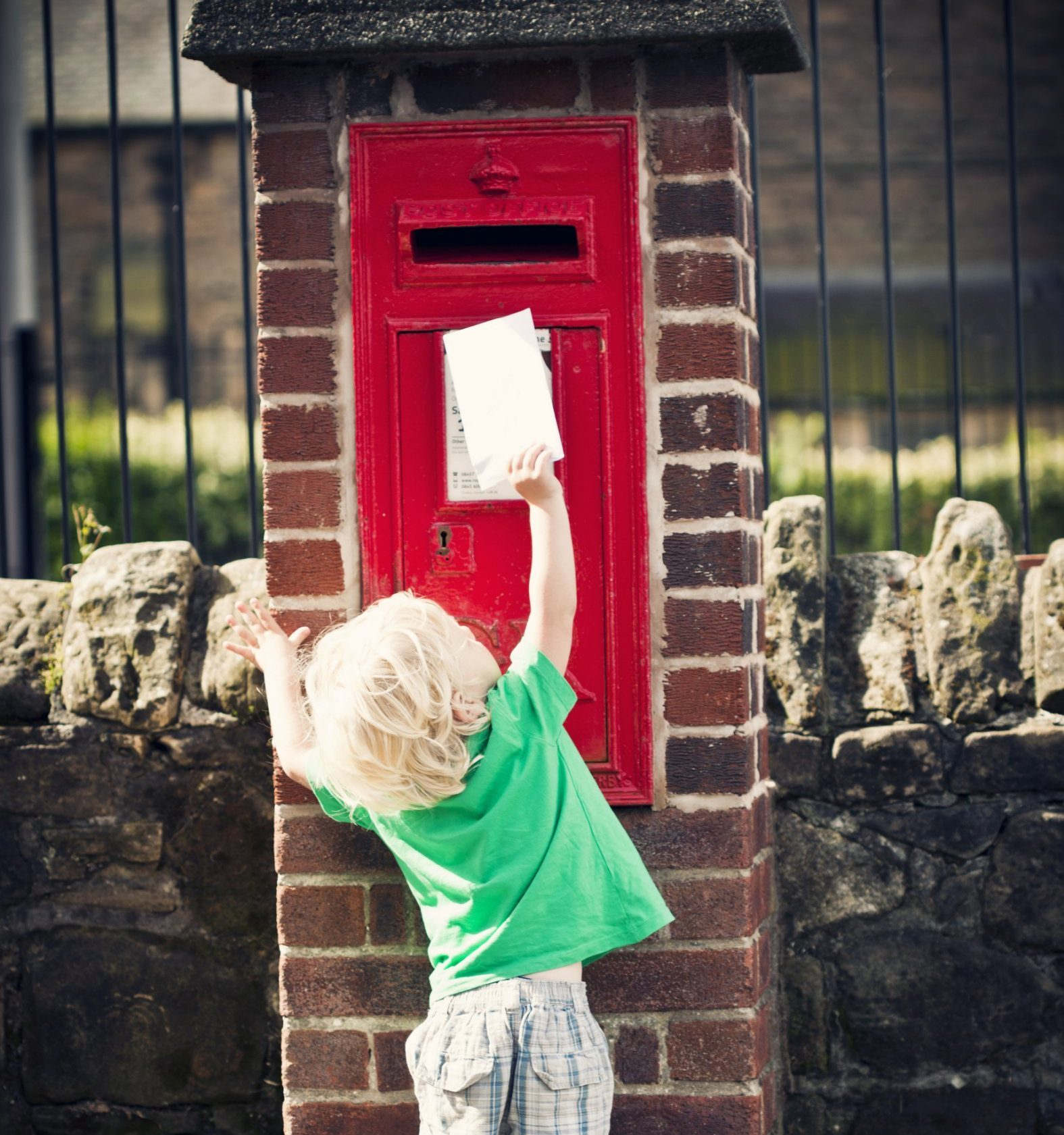 Little boy (3yrs) reaching up to post letter into post box.