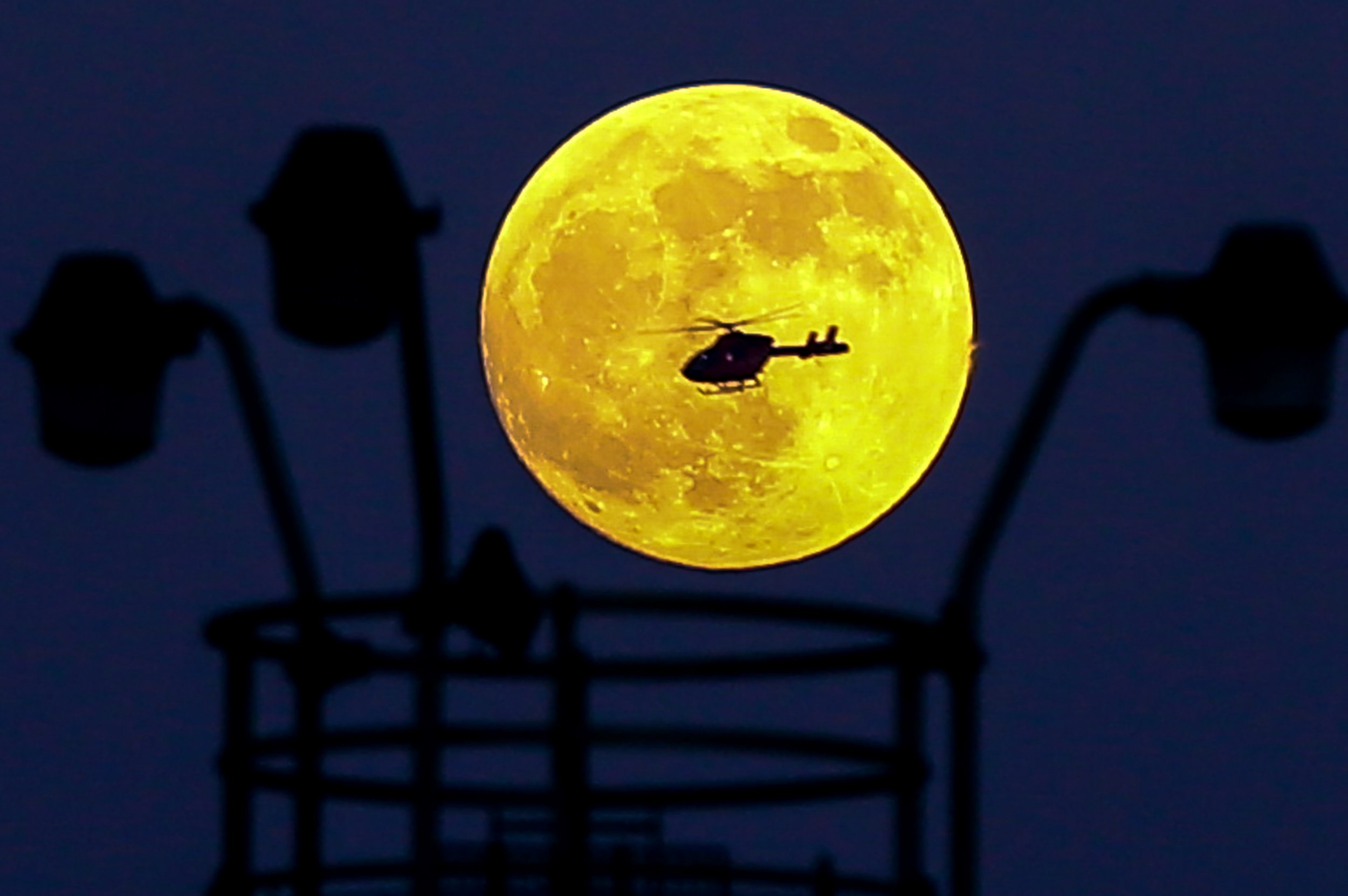 Mandatory Credit: Photo by Dinendra Haria/REX (10069292d) A helicopter flies in front of the Wolf Moon as it rises over the capital. The Wolf Moon, the Full Moon on January 20-21, 2019, is a Supermoon, making it look bigger and brighter than usual during the total lunar eclipse. 'Wolf Moon' rising over London, UK - 20 Jan 2019