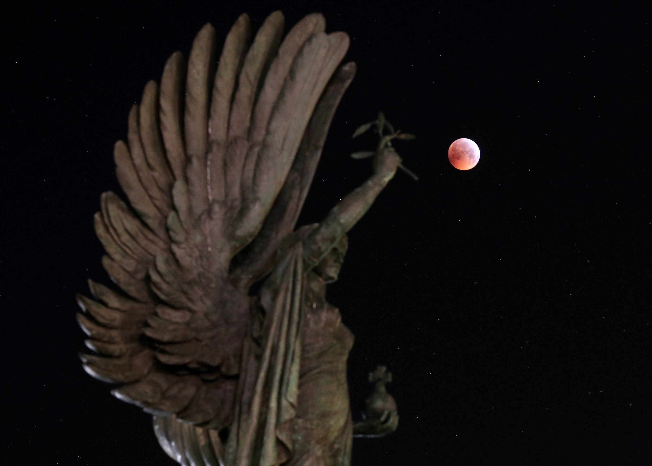 """EDITORS NOTE LONG EXPOSURE A super blood wolf moon over the peace statue on Brighton seafront during a lunar eclipse. PRESS ASSOCIATION Photo. Picture date: Monday January 21, 2019. A total lunar eclipse colours the lunar surface a reddish hue at the same time it appears brighter and closer to earth than normal, seeing phenomena known as a blood moon and supermoon combine. And in January, the full moon is sometimes labelled a """"wolf"""" moon, creating the unusual celestial label which seems to have stuck. See PA Story SCIENCE Eclipse. Photo credit should read: Andrew Matthews/PA Wire"""