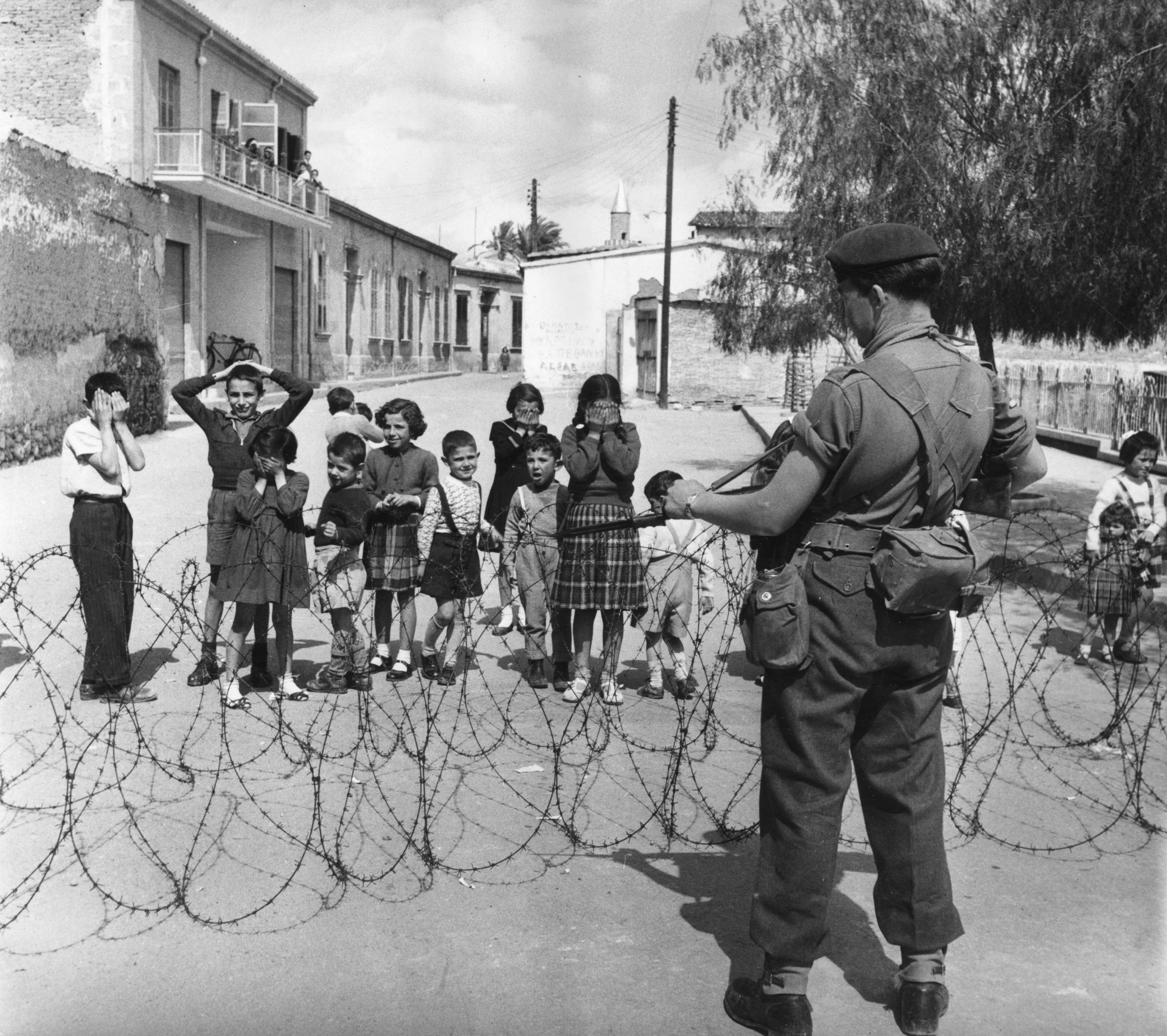 7th April 1956: The net closes on EOKA terrorists in the mountainous districts of Cyprus, as a British Marine guards the road and bewildered children look on. The move follows the failure of intergovernmental talks over the future of the territory. Original Publication: Picture Post - 8314 - Terrorist Hunt In Cyprus - pub.1956 (Photo by Bert Hardy/Picture Post/Getty Images)