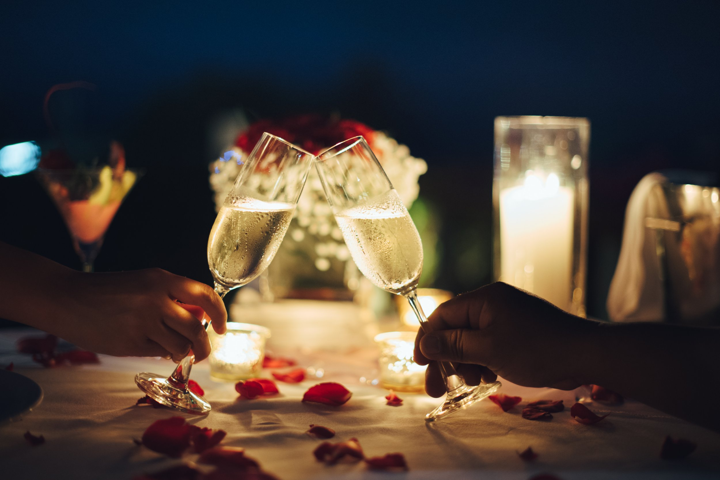 Romantic candlelight dinner table setup. Man & Woman hold glass of Champaign.; Shutterstock ID 1010722126; Purchase Order: -