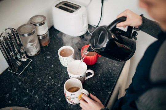 A woman prepares cups of tea in the office kitchen.
