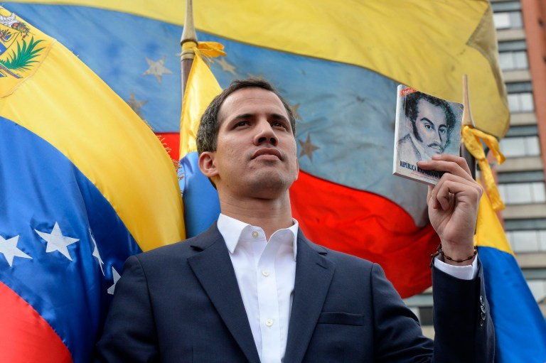 """TOPSHOT - Venezuela's National Assembly head Juan Guaido declares himself the country's """"acting president"""" during a mass opposition rally against leader Nicolas Maduro, on the anniversary of a 1958 uprising that overthrew military dictatorship in Caracas on January 23, 2019. - Moments earlier, the loyalist-dominated Supreme Court ordered a criminal investigation of the opposition-controlled legislature. """"I swear to formally assume the national executive powers as acting president of Venezuela to end the usurpation, (install) a transitional government and hold free elections,"""" said Guaido as thousands of supporters cheered. (Photo by Federico PARRA / AFP)FEDERICO PARRA/AFP/Getty Images"""