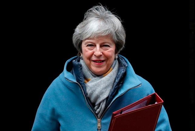 Theresa May holding a folder as she leaves 10 Downing Street in London.