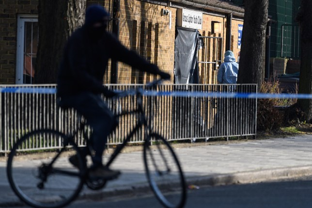 A person on a bike cycles past a crime scene