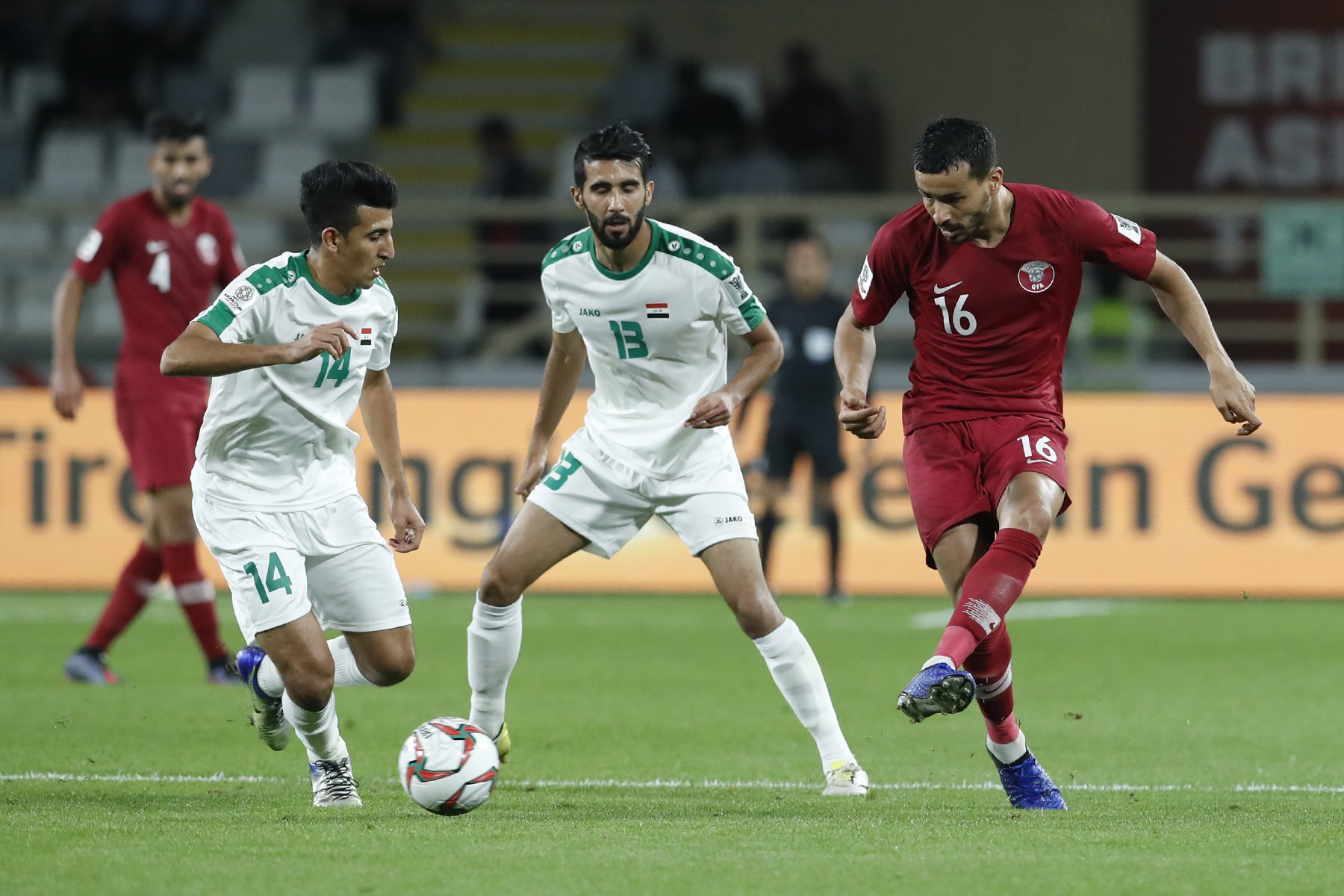 Qatar's midfielder Boualem Khoukhi, right, kicked the ball past Iraq's Midfielder Amjed Attwan, left, and Iraq's Midfielder Bashar Resan, during the AFC Asian Cup round of 16 soccer match between Qatar and Iraq at Al Nahyan Stadium in Abu Dhabi, United Arab Emirates, Tuesday, Jan. 22, 2019. (AP Photo/Hassan Ammar)