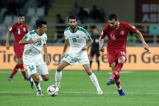 Qatar's midfielder Boualem Khoukhi, right, kicked the ball past Iraq's Midfielder Amjed Attwan, left, and Iraq's Midfielder Bashar Resan, during the AFC Asian Cup round of 16 soccer match between Qatar and Iraq at Al Nahyan Stadium in Abu Dhabi, United Arab Emirates, Tuesday, Jan. 22, 2019. (AP Photo/Hassan Ammar)