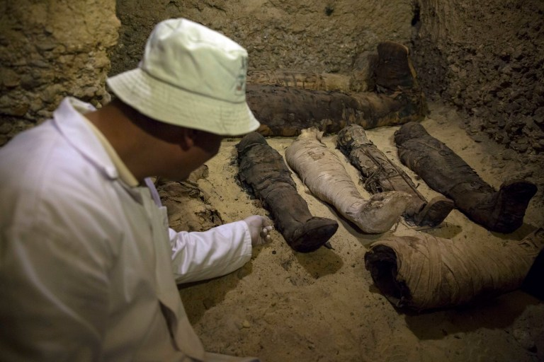 An archeologist inspects a recently discovered burial chamber in the desert province of Minya, south of Cairo, Egypt, Saturday, Feb. 2, 2019. On Saturday Egypt announced that it found a number of ancient burial chambers cut in rock, carrying about 40 mummies that are in good shape, along with pottery, papyri and exquisite mummy cases. Officials told reporters at the site that the chambers, which were cut out of rock, belonged to a middle-class family that probably lived during the Ptolemaic, early Roman or Byzantine period. (AP Photo/Roger Anis)