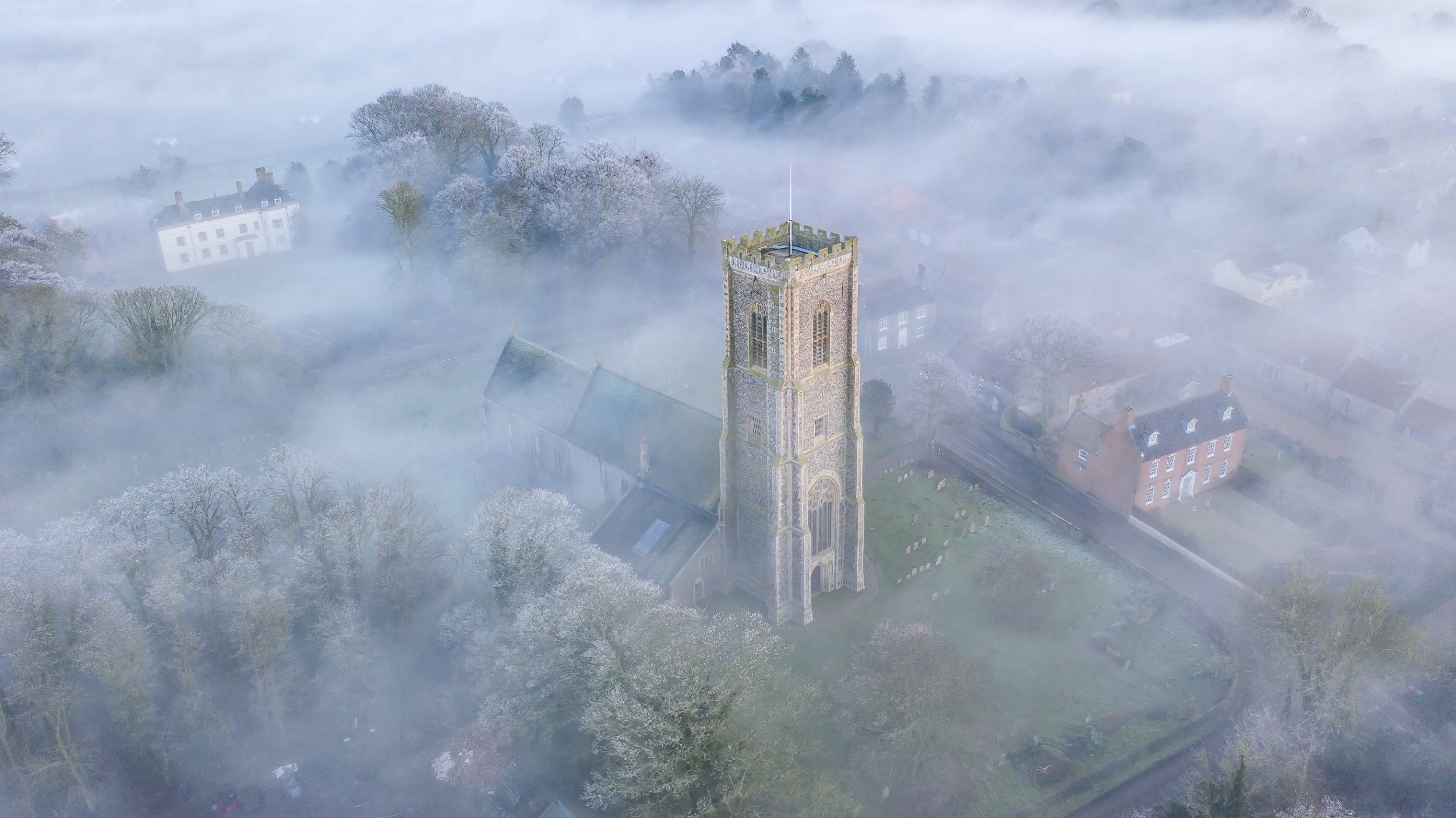 Fog around St James Parish Church in Southrepps, Norfolk which was captured in a drone video. See SWNS copy SWCAfog: This stunning drone footage shows a church spire rising from thick 'radiation fog' covering a village at sunset. The majestic scene was captured in the small community of Southrepps, Norfolk on Friday afternoon. Radiation fog - where cold land cools the air moving over it causing its moisture to condense - can be seen settled in a thick blanket over the houses.
