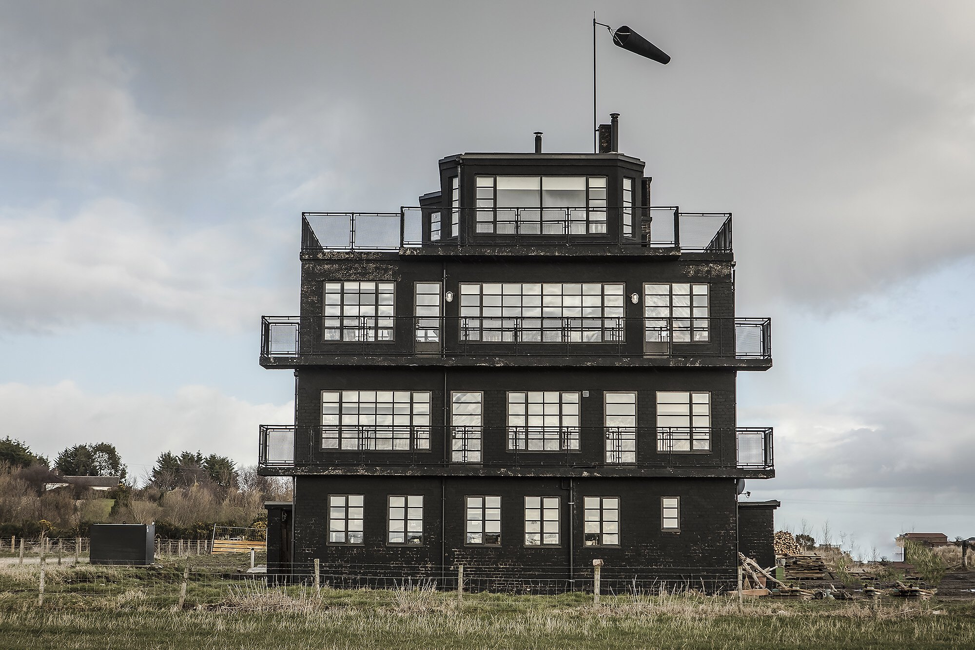 """Calling all history buffs; you can now stay overnight in a former air control tower that served as a unique outpost during WWII. Sitting on a former air base in Tain, next to the North Coast 500 Scenic Route, The HMS Owl Air Control Tower sits against the contrasting Scottish Highlands as is available to stay in via Airbnb. The former military structure, which is located on the original WWII airway, has emerged from a five-year renovation by owners Justin Hooper and Charlotte Seddon to convert it into a family home and guesthouse, successfully shaping it into a cozy living space that maintains its uniquely upcycled war-era glamour. Host Charlotte explained, """"The control tower had been left derelict for decades and we took on its restoration, and much of the labor, as a passion project and the most important thing for us was to preserve the raw, bruised, but not broken feel of the building."""" Donning a matte-black exterior, the structure retained its original steel-framed Crittall windows throughout the renovation process, with exposed brick walls and a collection of antique and factory-esque fixtures that compliment the historical structure???s barebones. While the project is indeed a family home, there is a room on the top floor where guests can enjoy a dreamlike view of the unspoiled landscape. Interiors hone a rugged industrial feel: concrete pillars, ceilings and floors contrast exposed brickwork. Warmer touches come in the form of leather and wooden furniture and a wood burning stove which takes pride of place in the living room. Charlotte continued, """"We rebuilt the Black Nissen hut adjacent to the tower which is also newly available to rent. We put them both on Airbnb as we wanted to be open to a large audience from the off and see what happened! It's gone well so far and guests seem to really enjoy their stays in both the tower and the Black Nissen."""" Rates for the room on the top floor start from ??75 per night which comes complete with far-reaching v"""