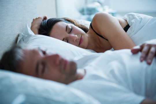 Falling in love will help you sleep better, science says Serene couple sleeping in bed