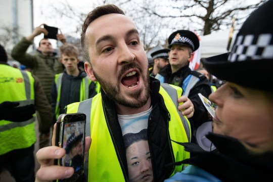 "? Licensed to London News Pictures . 09/02/2019. Manchester , UK . JAMES GODDARD (wearing a Kim Jong Un shirt) live streams video using his mobile phone as he leads a "" Yellow Vest "" protest in Manchester City Centre . The yellow vest concept has been adopted from French demonstrators by some British groups in support of Brexit , Donald Trump and former EDL leader Stephen Yaxley-Lennon - aka Tommy Robinson . A similar demonstration in the city in January was ridiculed after protesters were kettled by police in front of a branch of Greggs the Baker . Photo credit : Joel Goodman/LNP"
