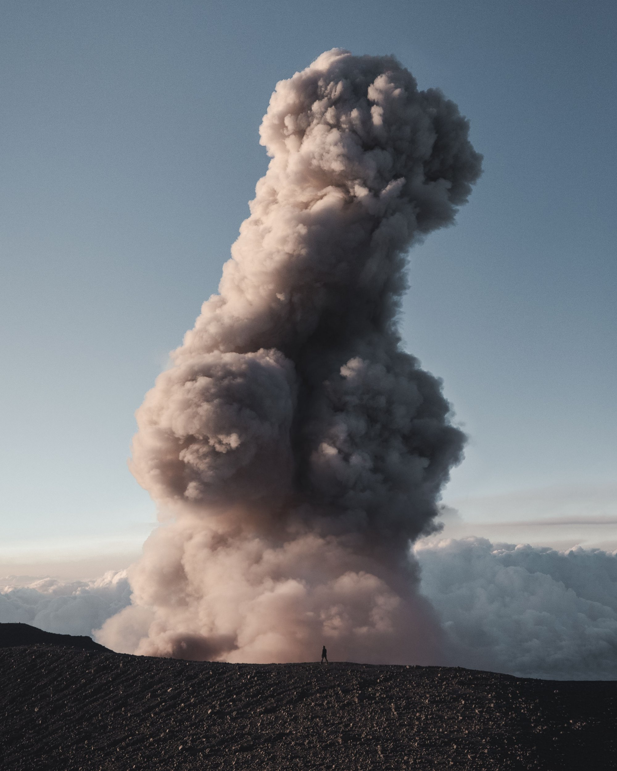 Pic by Josiah Gordon/Caters News - (Pictured: Josiah stands in the shadow of the gigantic phallic shaped eruption.) -Two hikers were left red-faced after an Indonesian volcano erupted in the shape of a giant penis. Adventure enthusiast and photographer, Josiah Gordan, 23, was climbing Javas highest active volcano, Semeru, with friend, Megan Hassa when the eruptions began. After a two-day hike to reach the top, Josiah and Megan were admiring the view below, when the lava began spewing into the air only a few hundred feet from where they were standing. But the pairs awe quickly turned to blushes after the smoke cloud quickly transformed into a phallic shape. SEE CATERS COPY.